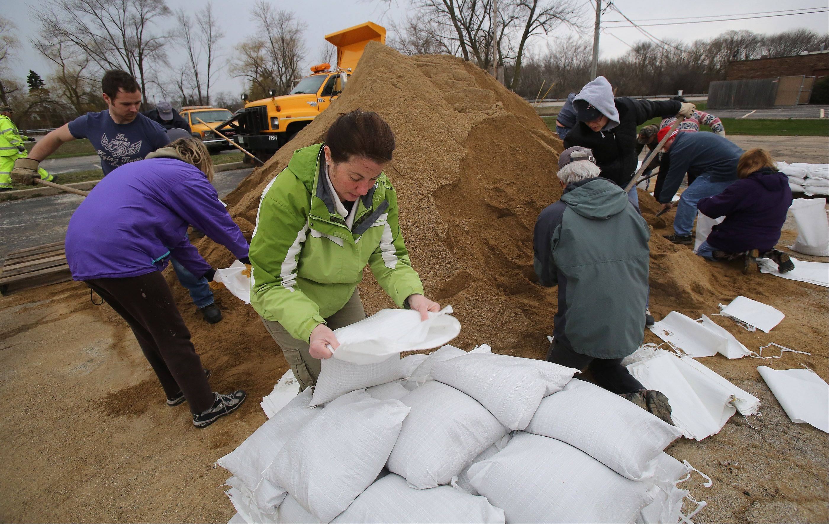 Gurnee resident Sue Tebbetts places a sandbag on a pile as volunteers fill sandbags in Gurnee yesterday to help area residents and businesses from the flooding caused by the Des Plaines River. Heavy rains are expected to continue today, causing the problem to become worse.