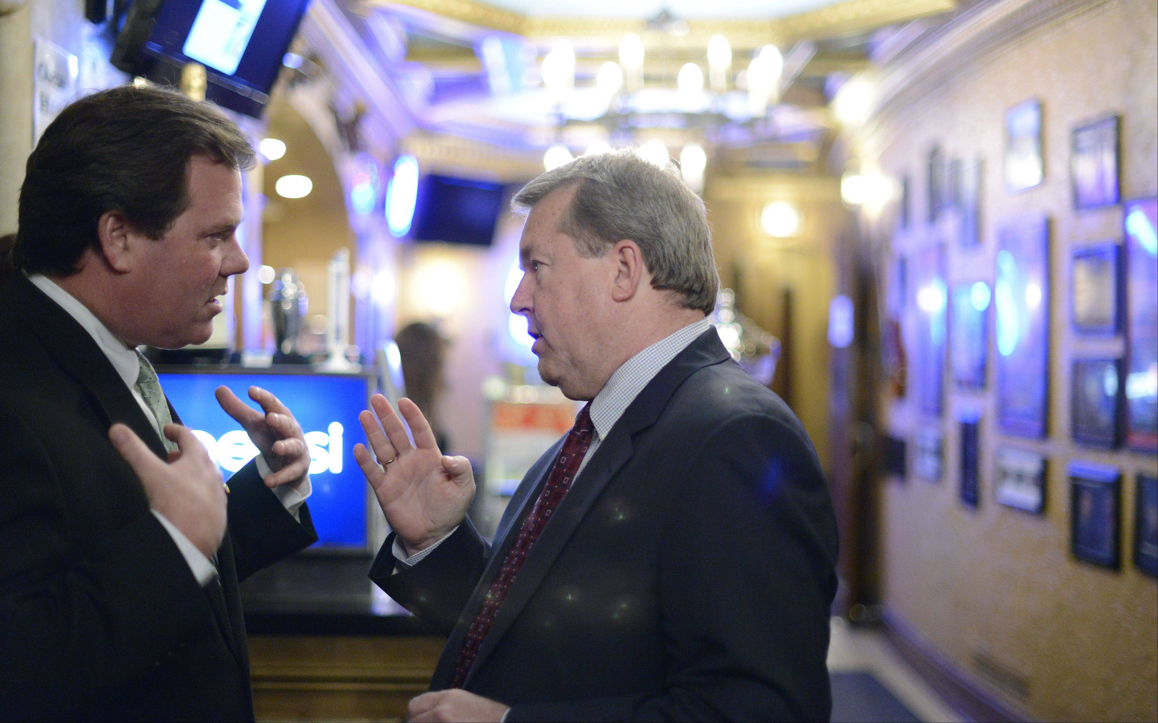 Geneva Mayor Kevin Burns and St. Charles Mayor Don DeWitte chat Wednesday in the lobby of the Arcada Theatre at DeWitte's farewell party.