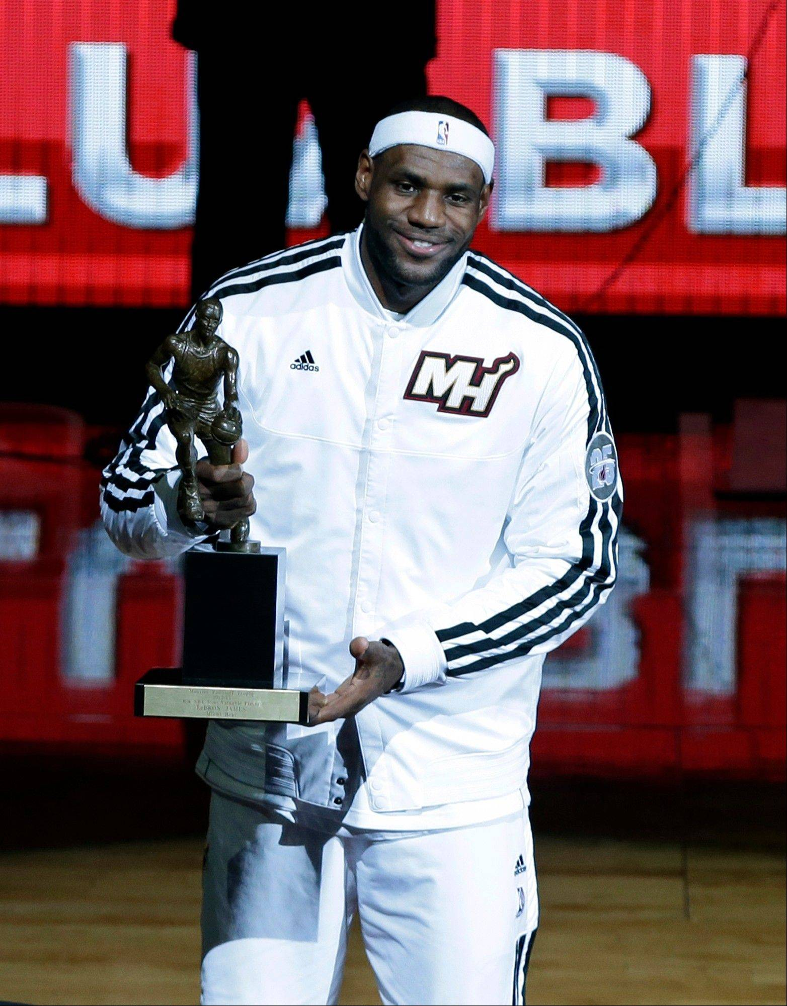The Heat's LeBron James displays the fourth NBA MVP trophy of his career Monday in Miami.