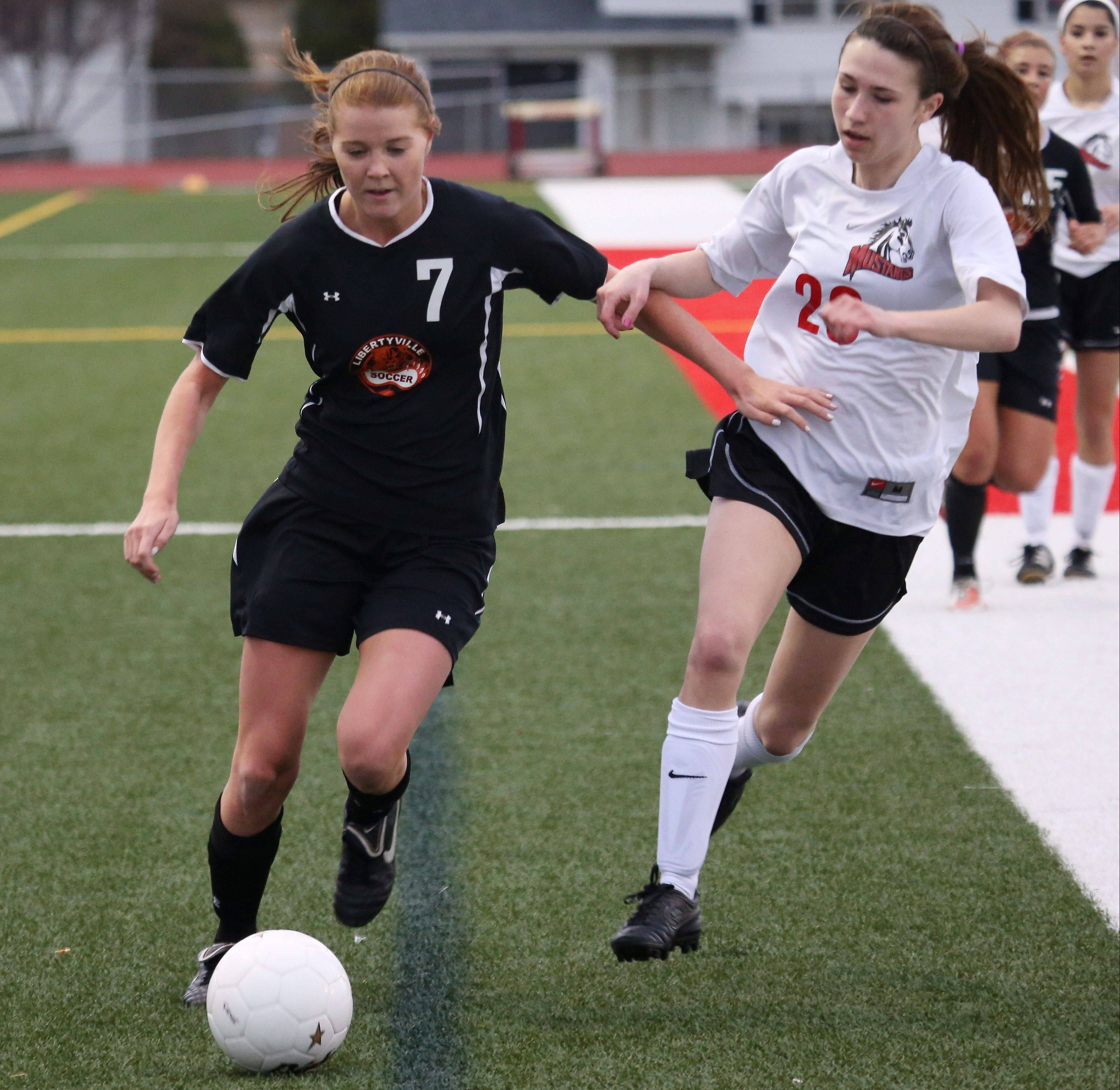 Libertyville forward Katie McAuliffe streaks downfield as Mundelein defender Jessica Schultz gives chase.