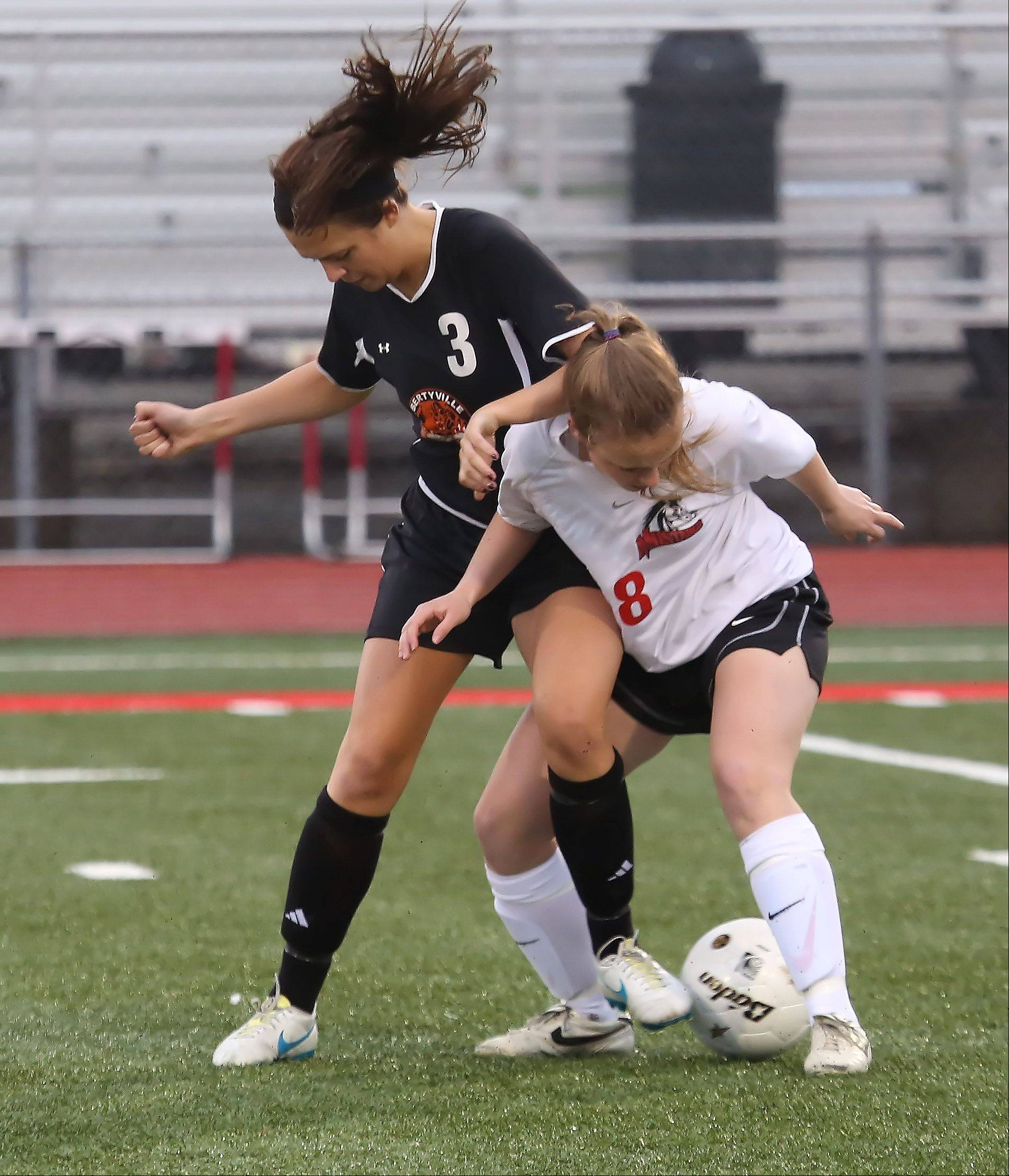 Mundelein midfielder Kelly Grove battles Libertyville midfielder Jessica Stanley Thursday at Mundelein.