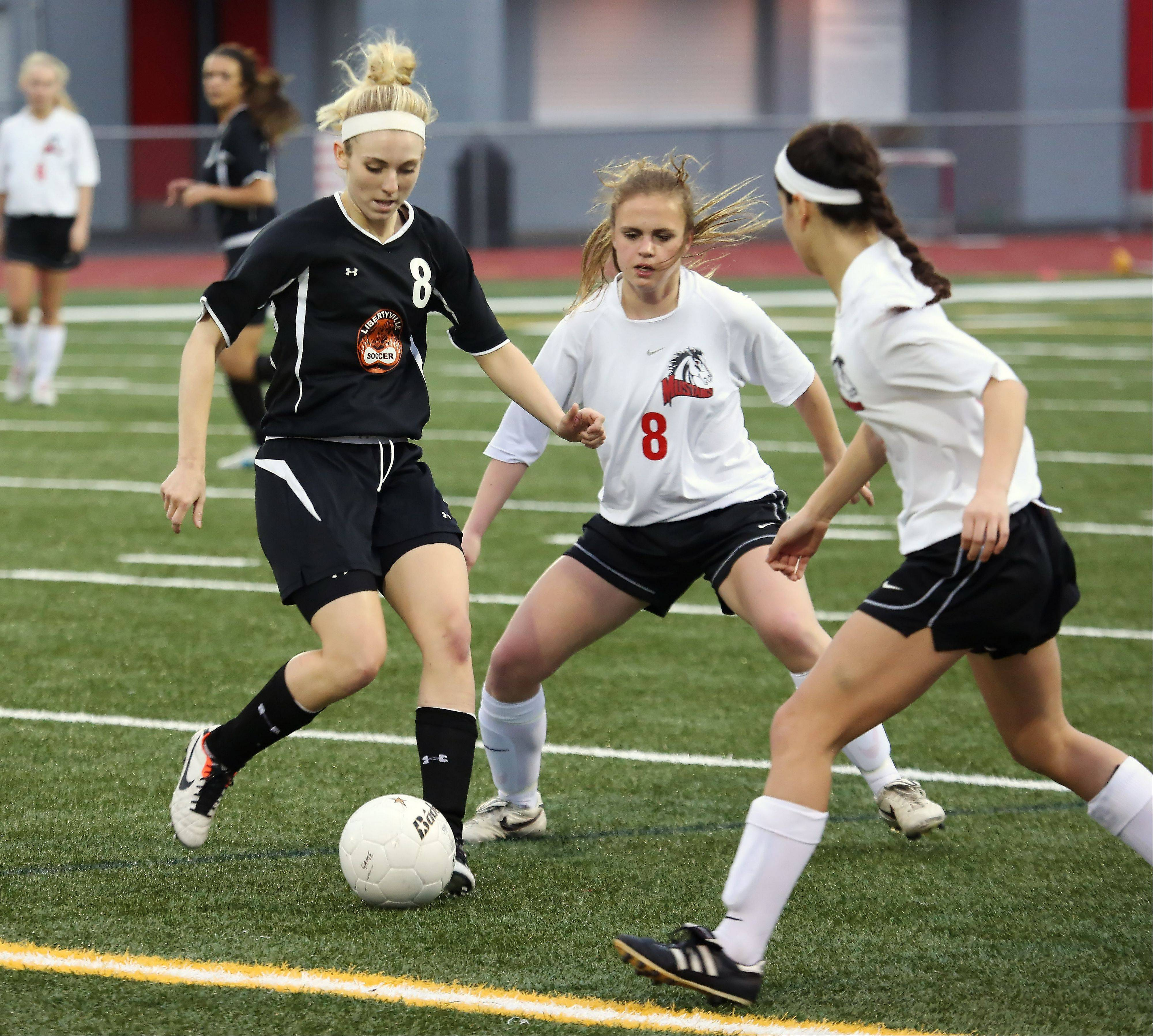 Libertyville midfielder Sam Marsh dribbles around Mundelein midfielder Kelly Grove on Thursday at Mundelein.