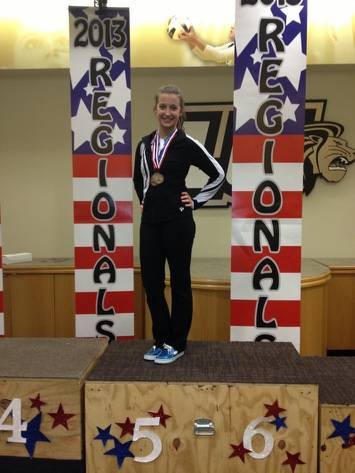 Melissa Jordan accepting her medals at regional gymnastics competition in St. Louis MO.