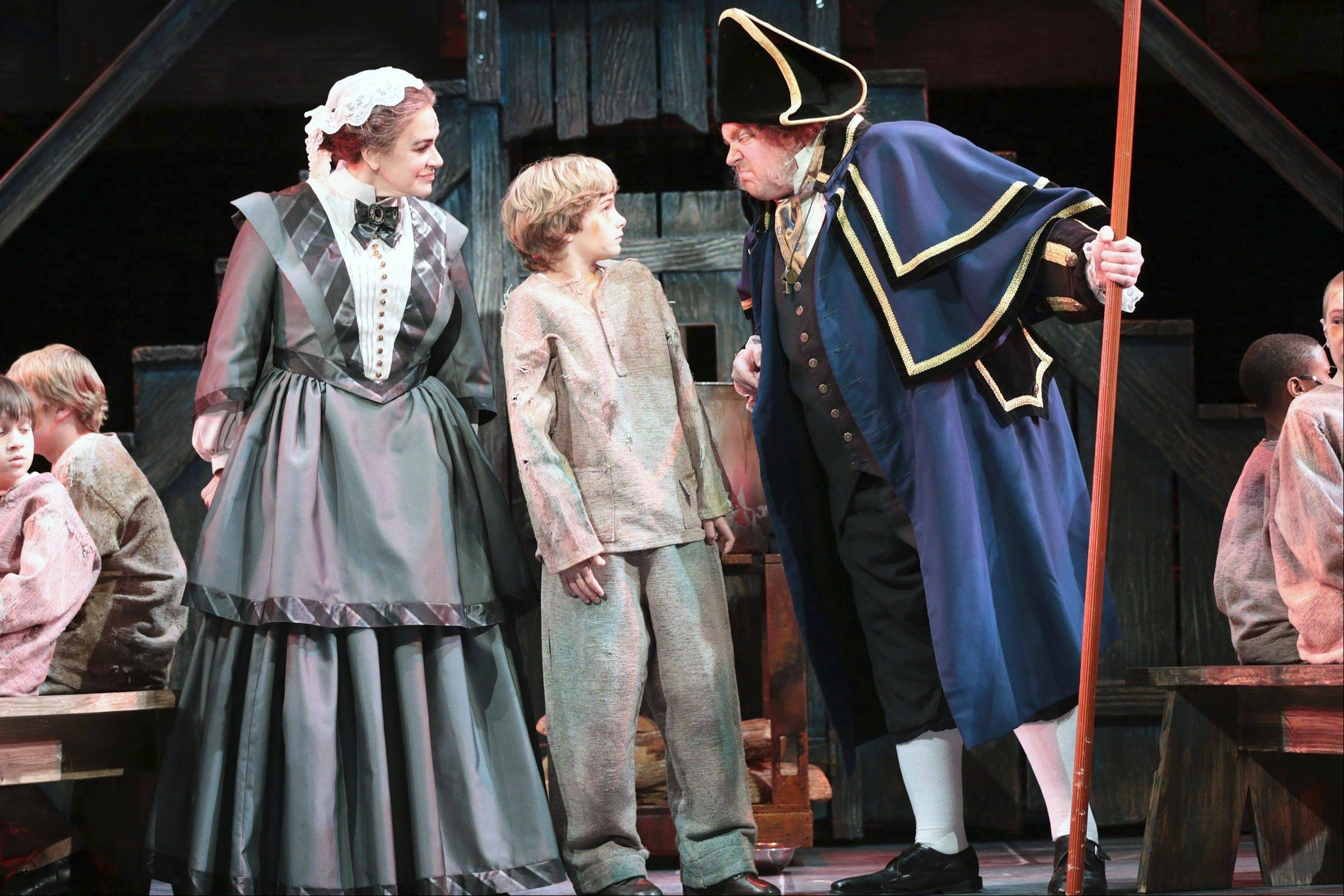 "Widow Corney (Catherine Smitko) and Mr. Bumble (Michael Lindner) can't believe that Oliver Twist (Brady Tutton, center) has asked for more gruel in Lionel Bart's 1960 musical ""Oliver!"" at Drury Lane Theatre in Oakbrook Terrace."