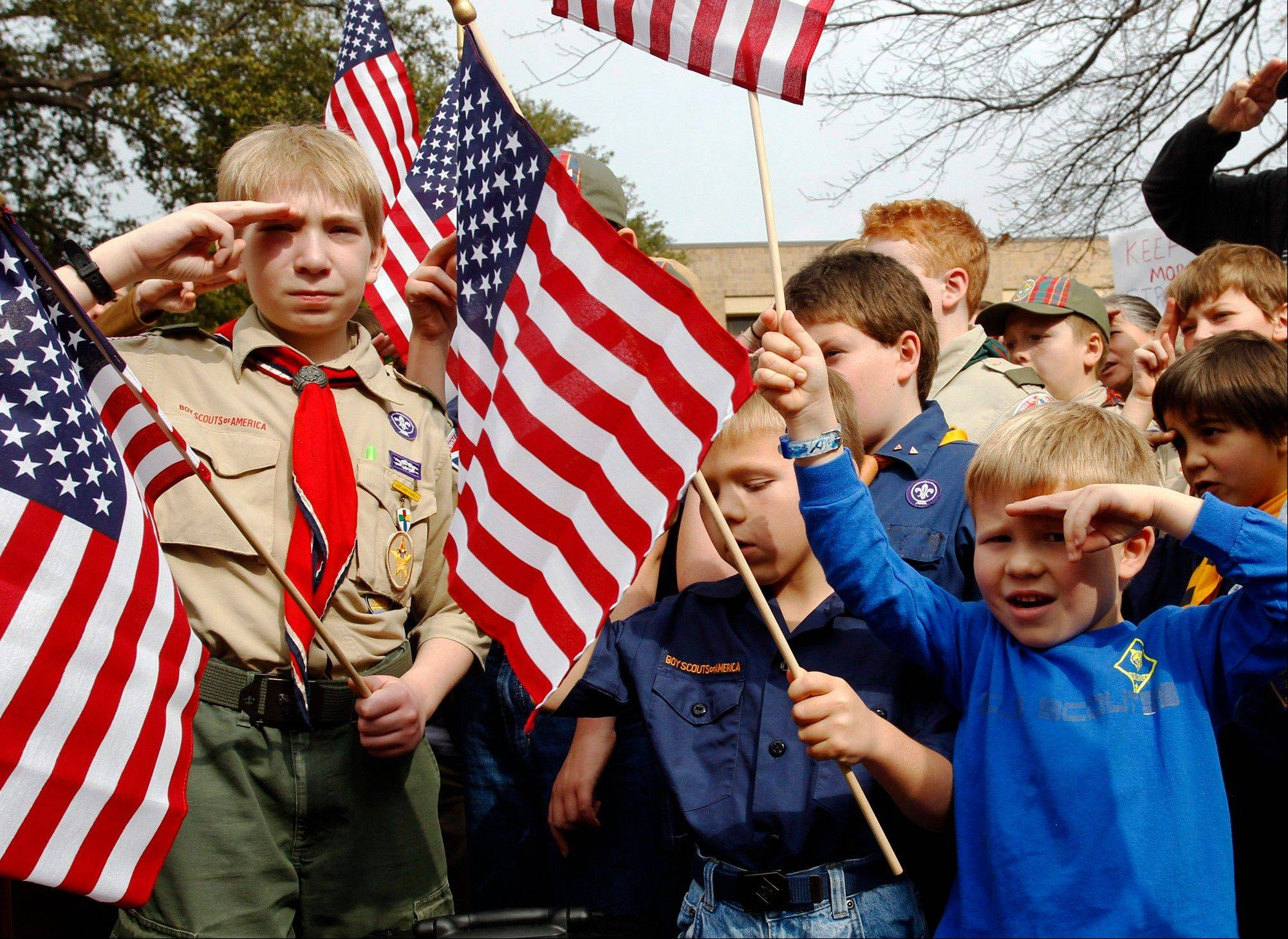 Associated Press/Feb. 6, 2013 From left, Joshua Kusterer, 12, Nach Mitschke, 6, and Wyatt Mitschke, 4, salute as they recite the pledge of allegiance during the �Save Our Scouts� prayer vigil and rally against allowing gays in the organization in front of the Boy Scouts of America National Headquarters in Dallas, Texas.