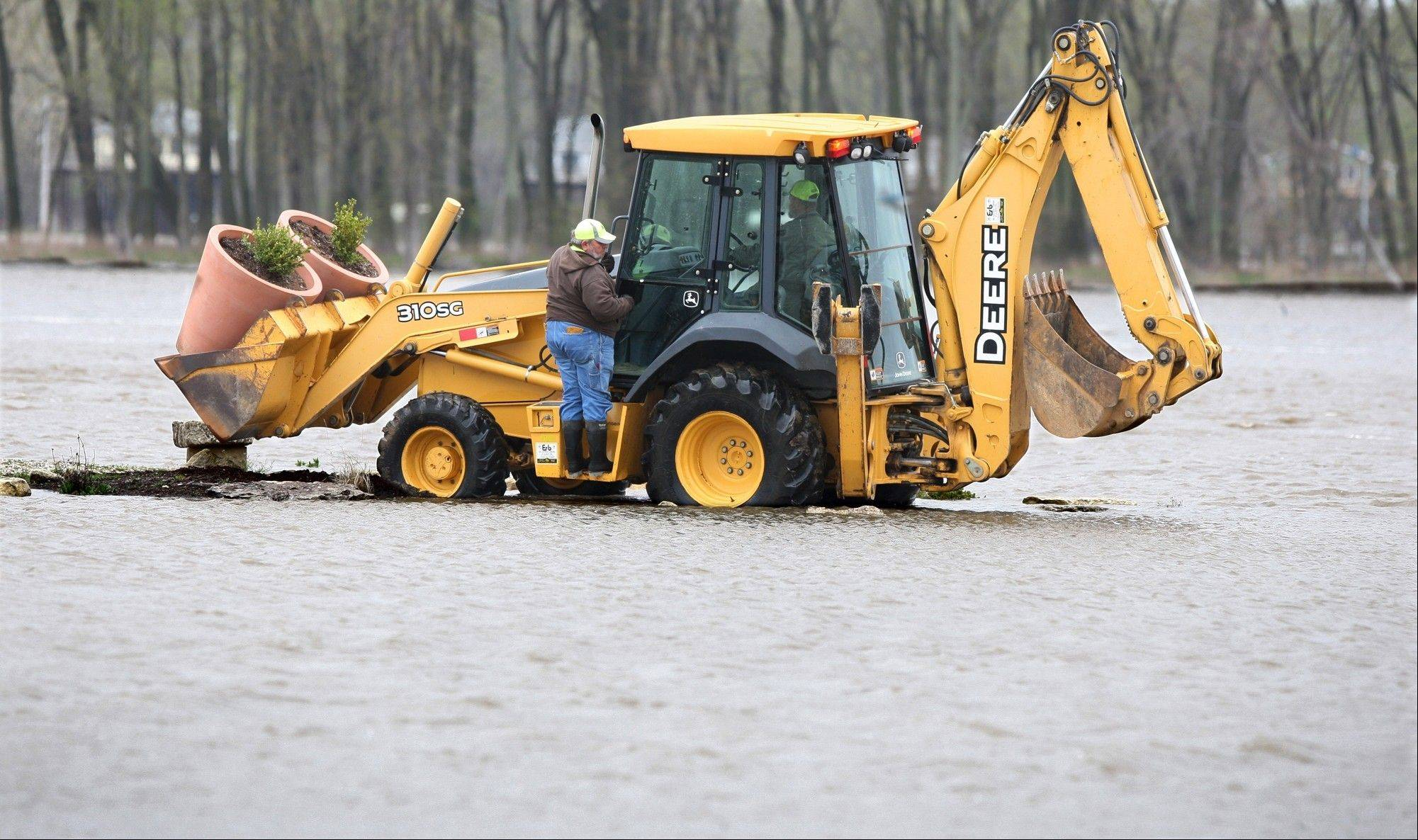 Grafton Public Works employees rescue two planters Friday from the already flooded riverfront in Grafton, Ill.