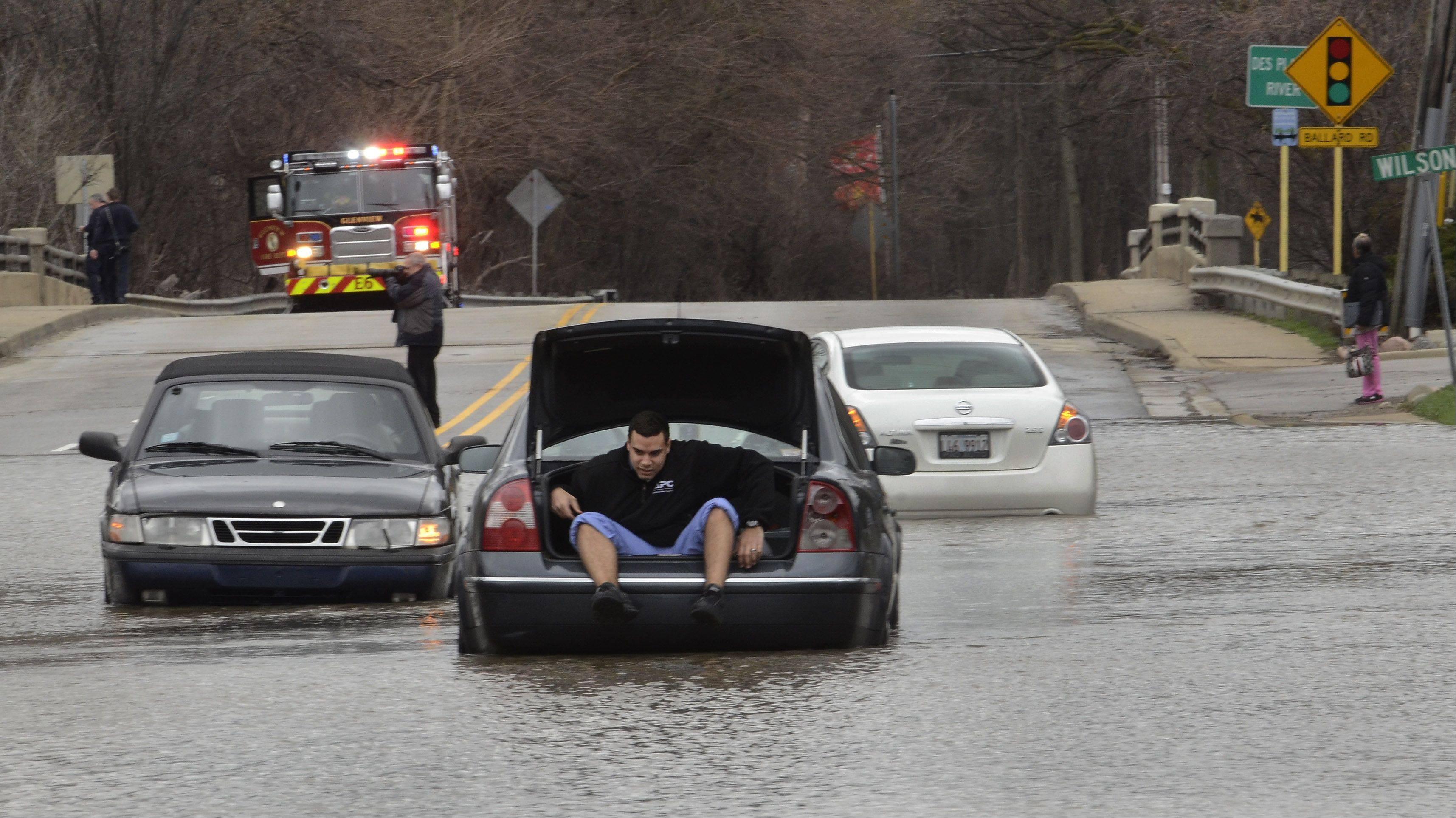Efrain Baez of Des Plaines crawls out the trunk of his Volkswagen after getting stuck in the flooded intersection of Rand and Wilson in Des Plaines.