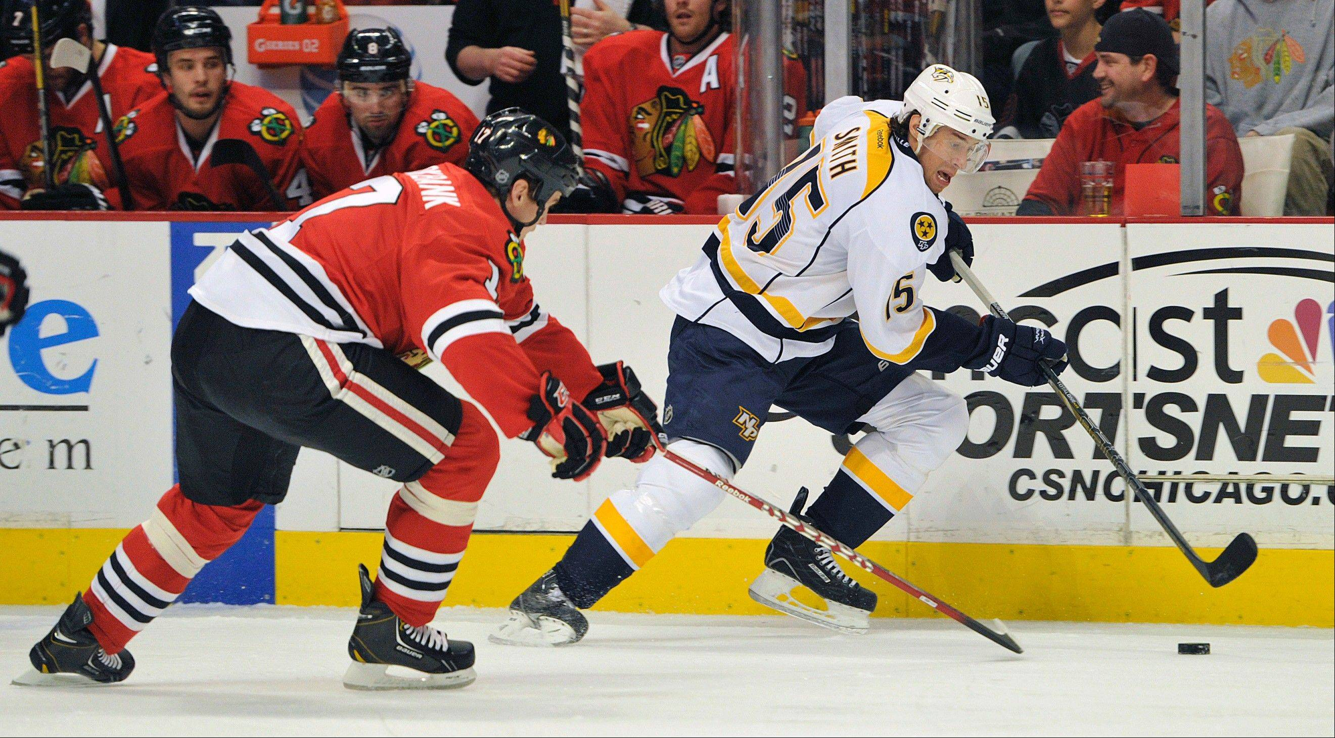 Chicago Blackhawks' Brent Seabrook, left, and Nashville Predators' Craig Smith (15) fight for the puck during the first period of an NHL hockey game Friday, April 19, 2013, in Chicago.
