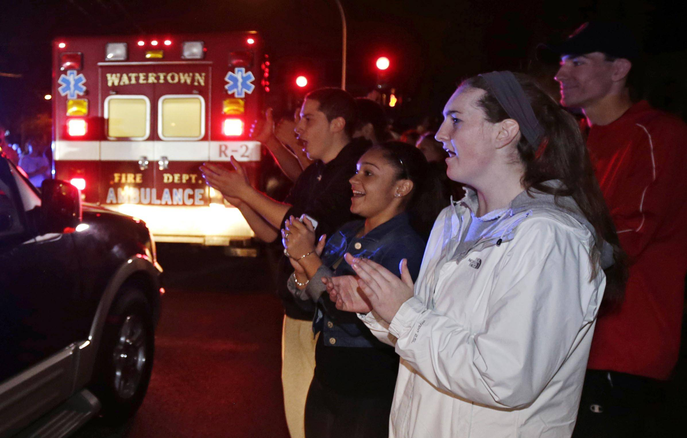A gathering of people applaud as first responders leave the scene after the arrest of a suspect of the Boston Marathon bombings in Watertown, Mass., Friday, April 19, 2013. Two suspects in the Boston Marathon bombing killed an MIT police officer, injured a transit officer in a firefight and threw explosive devices at police during their getaway attempt.