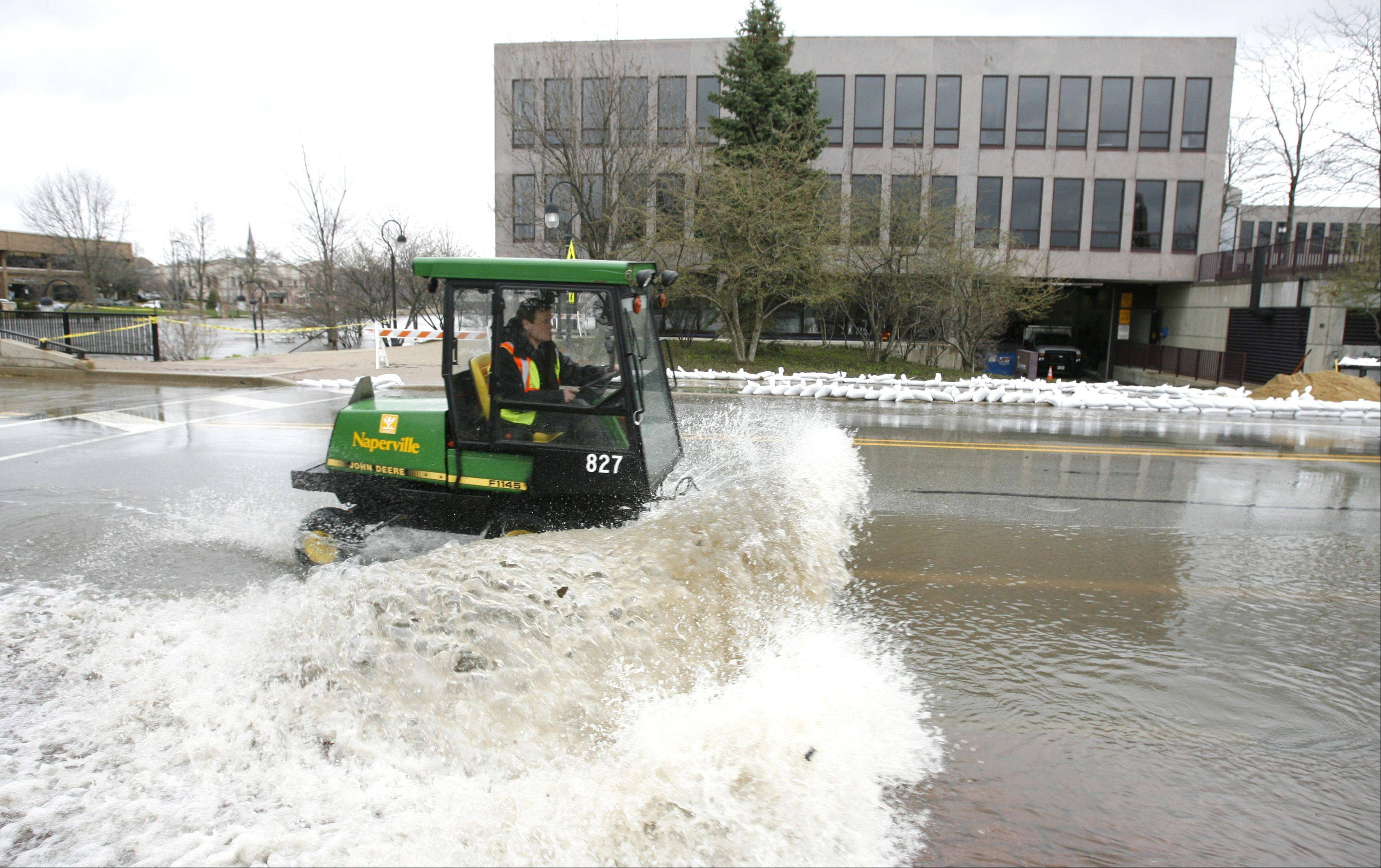 A city worker works to remove water near Naperville's city hall.