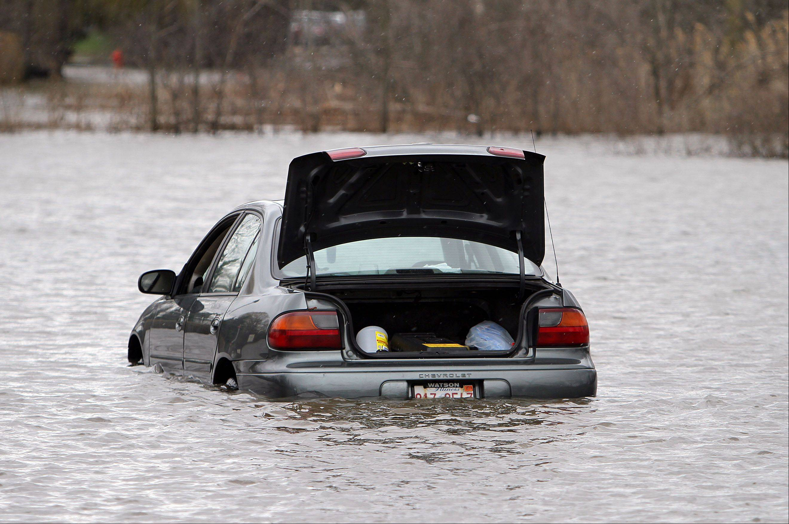 A car is stranded in the parking lot of Bank Financial near the entrance to the Lincolnshire Marriott Resort on Friday.