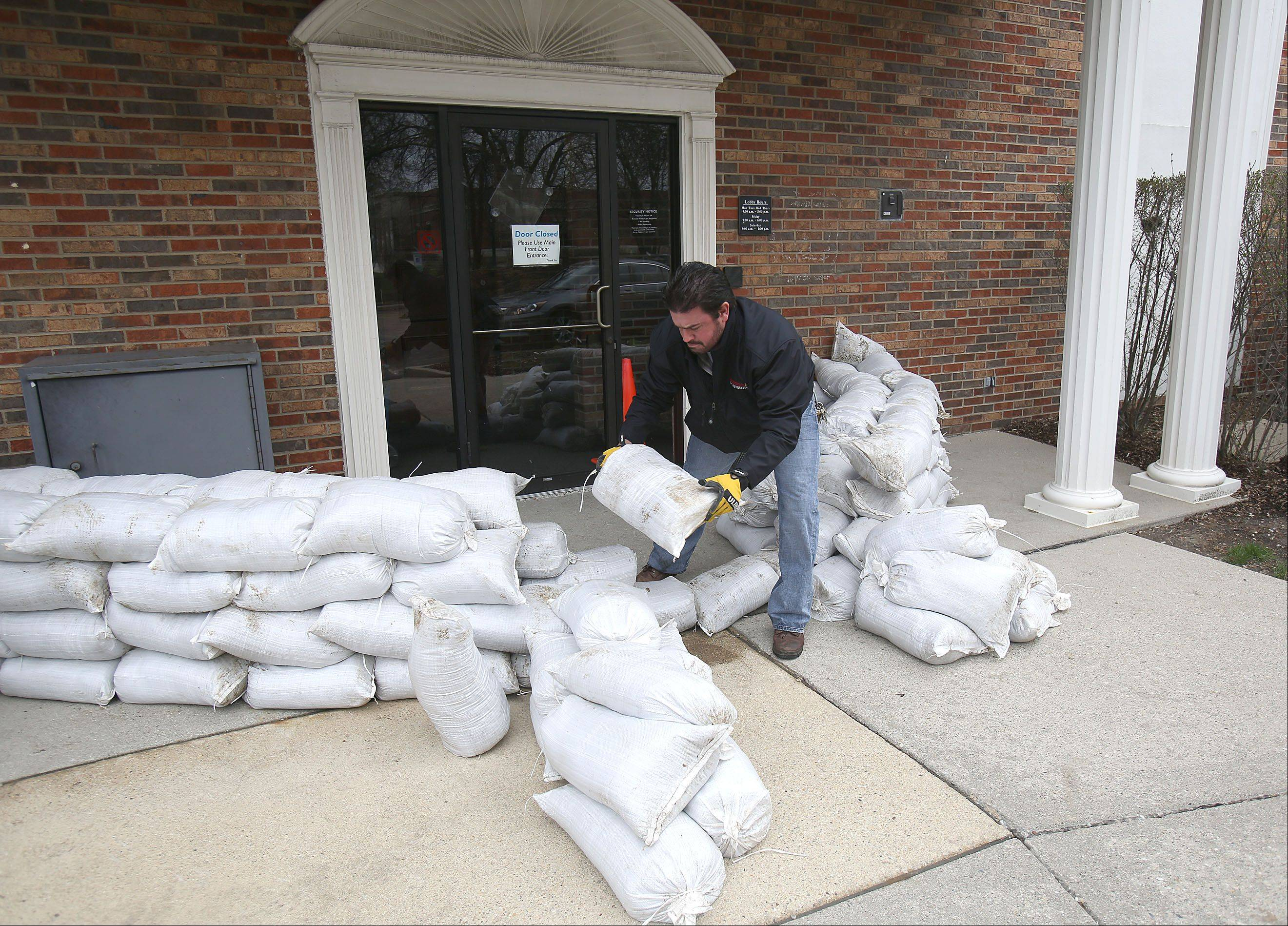 Casey Kilimnik stacks sandbags around the entrance to Bank Financial in Lincolnshire on Friday.
