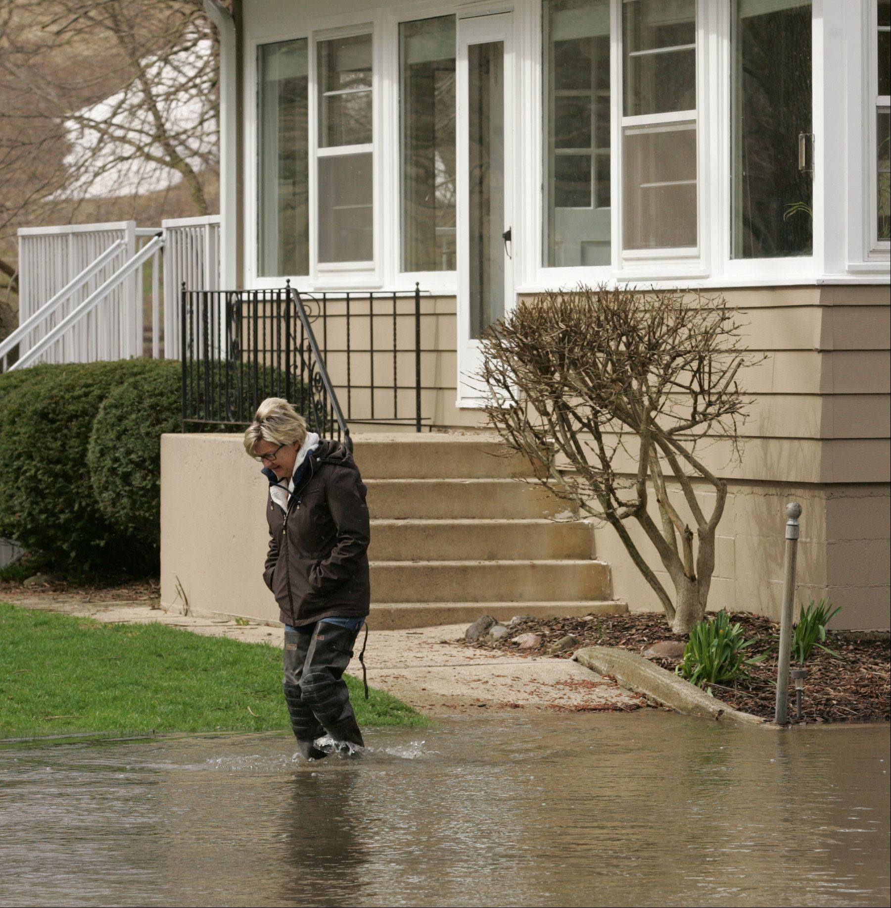 Nan Gagliano walks from her home along Wanaki Trail in Algonquin Friday morning where floodwaters have already surrounded her home. Despite the rising water, Gagliano says there's only moderate seepage in her basement. She and her husband, Nick, were most concerned with protecting the foundation of the home from the river's strong current.