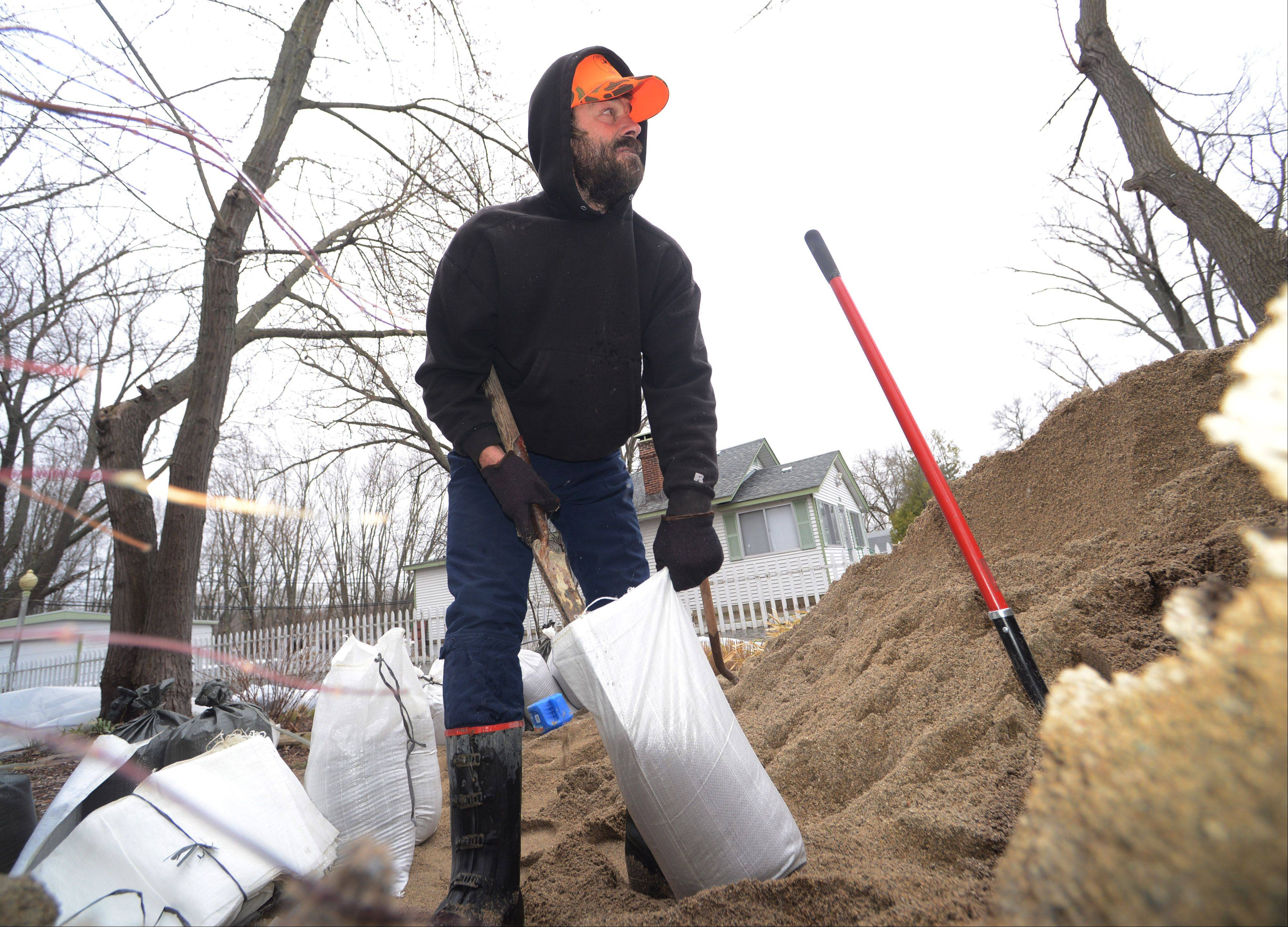 Paul Krueger fills sandbags at his Rawson Bridge Road home in Nunda Township near Island Lake Friday morning. Rising Fox River waters closed the road which crosses over the Fox River.