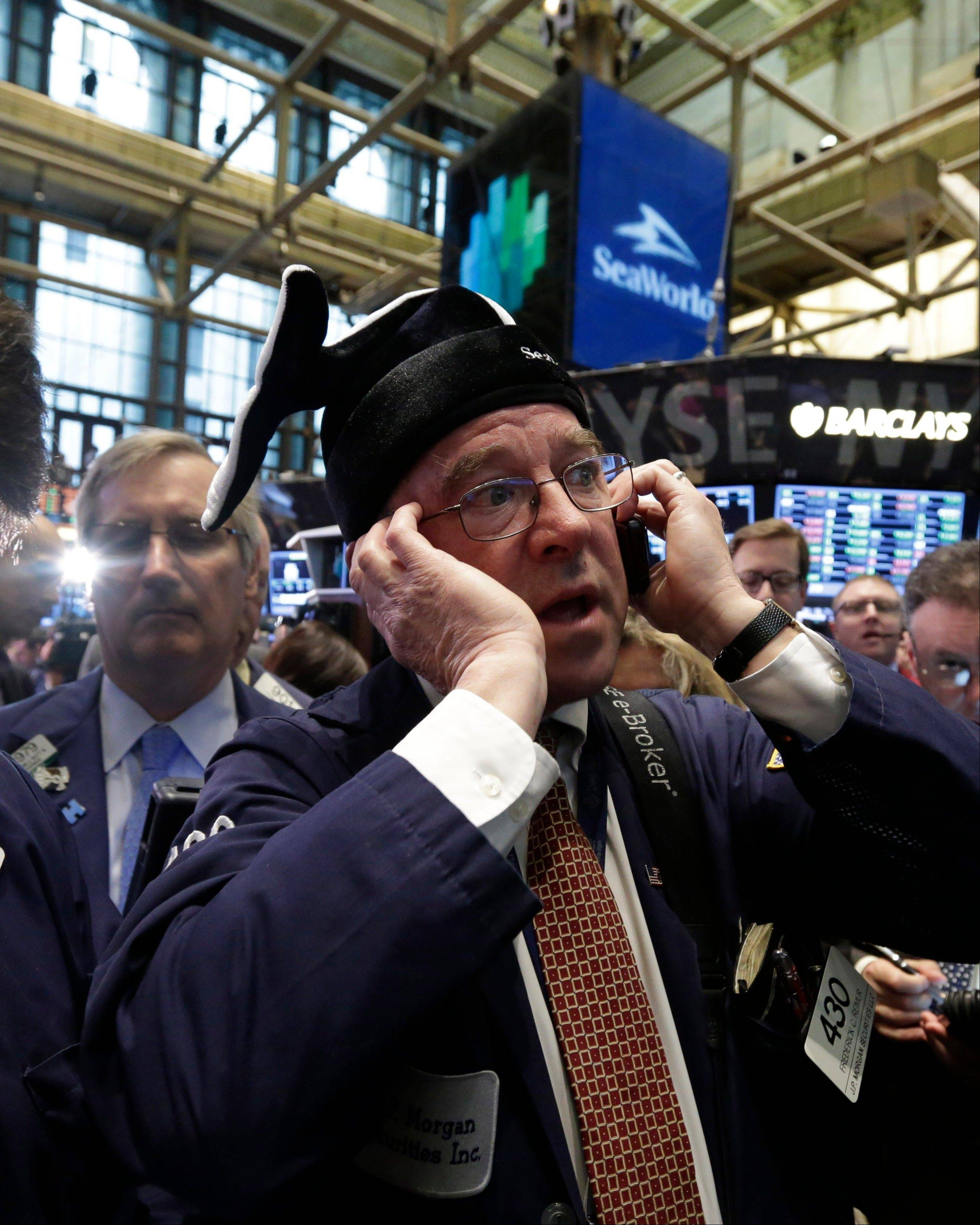 Trader Frederick Reimer, right, wears a whale cap Friday from Sea World as he waits for the company's IPO to begin trading, on the floor of the New York Stock Exchange.