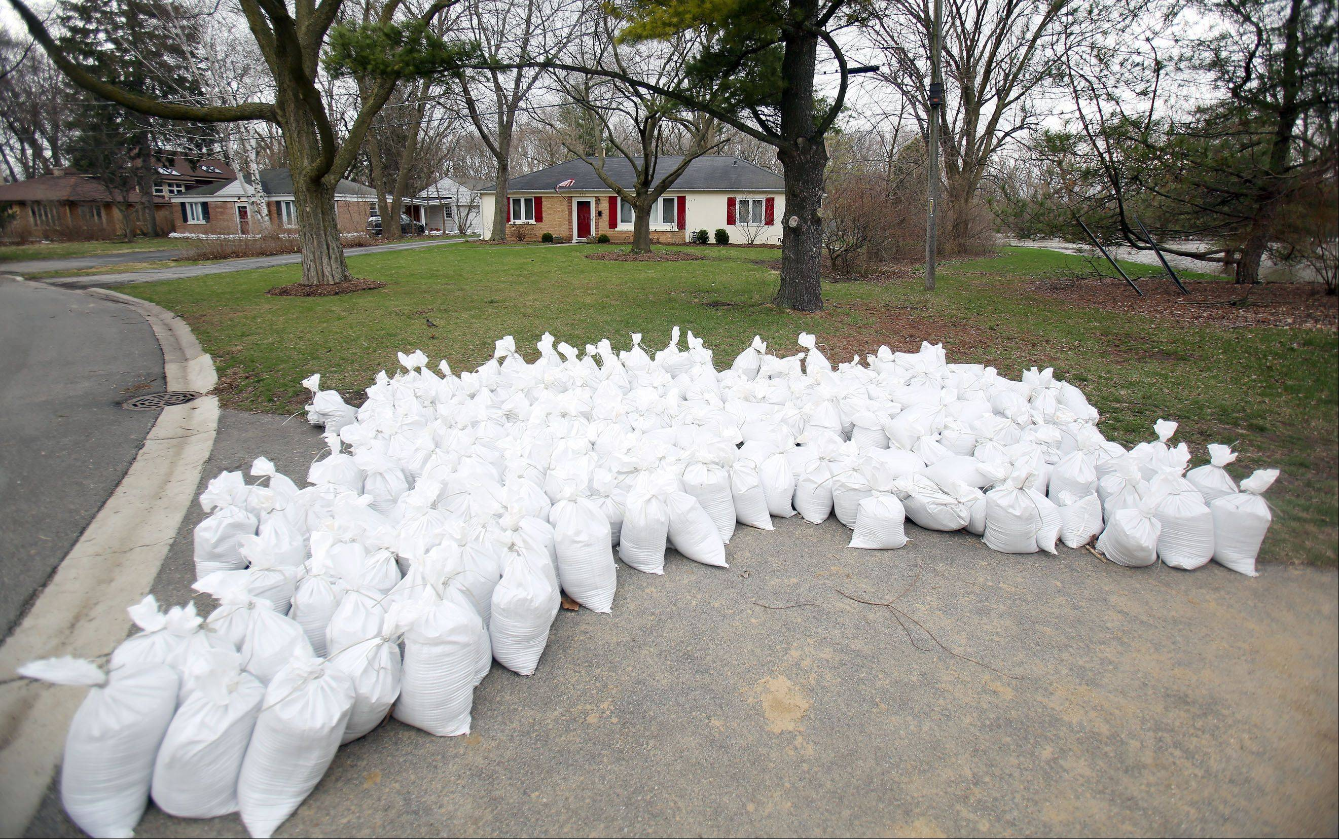 Sands bags sit in reserve at Riverside Park as the Des Plaines River continues to rise Friday morning in Libertyville.