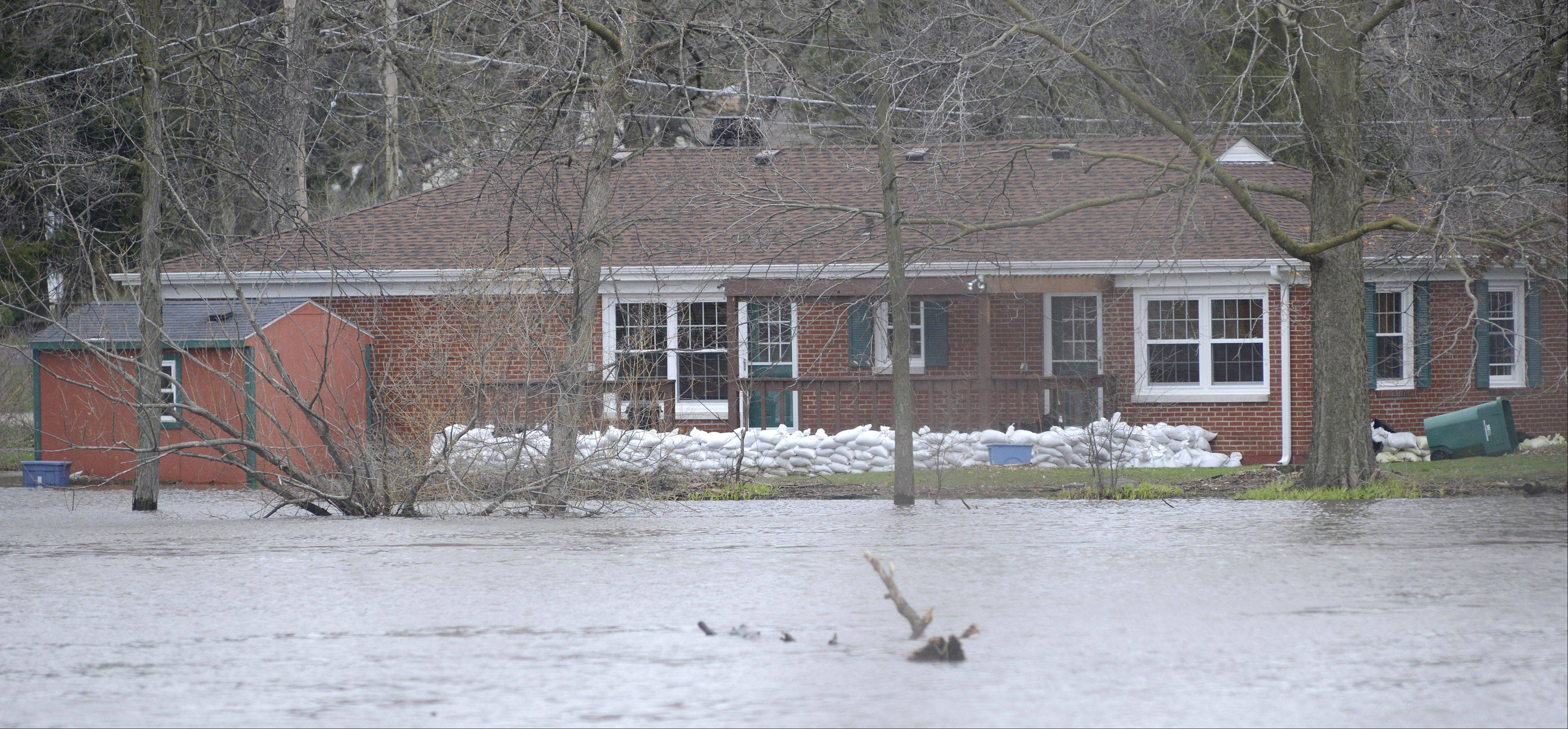 Homes on the west bank of the Fox River are prepared for rising waters in St. Charles on Friday, April 19. Waters have receded somewhat from yesterday judging by debris left behind.