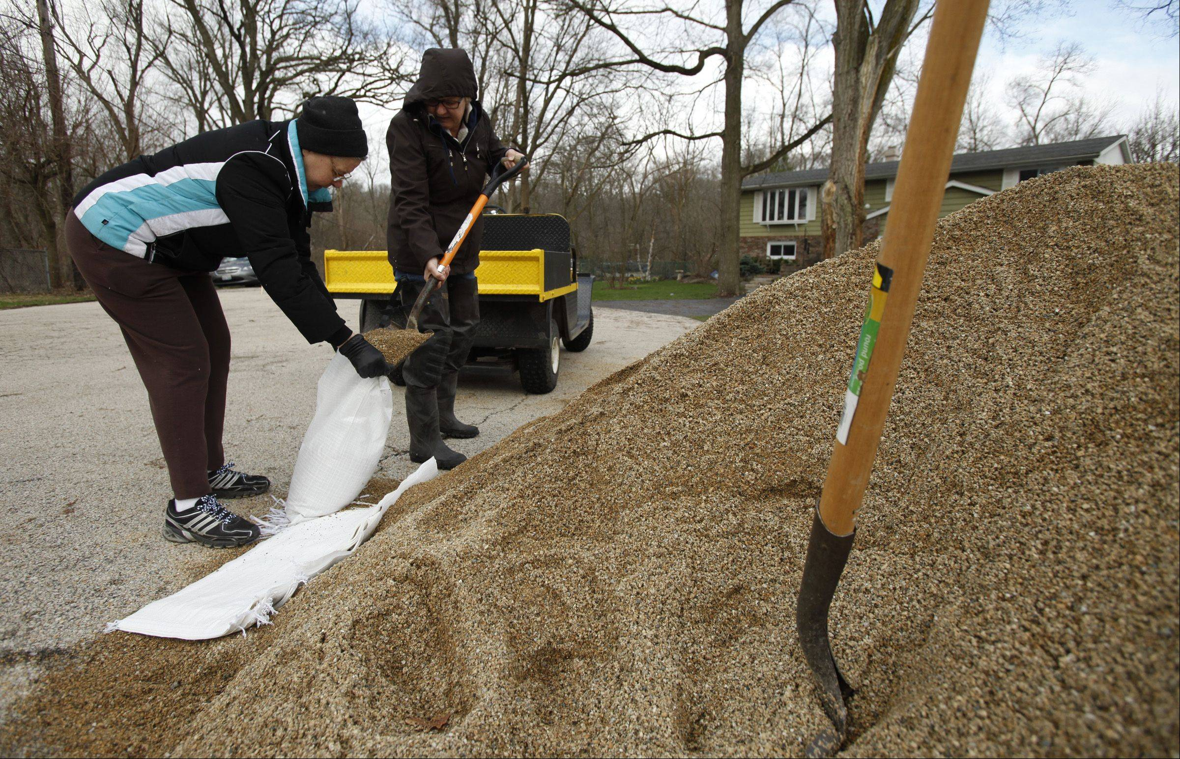 Yvonne Dragon, left, and Nan Gagliano fill sand bags near their homes on Algonquin's east side Friday morning.