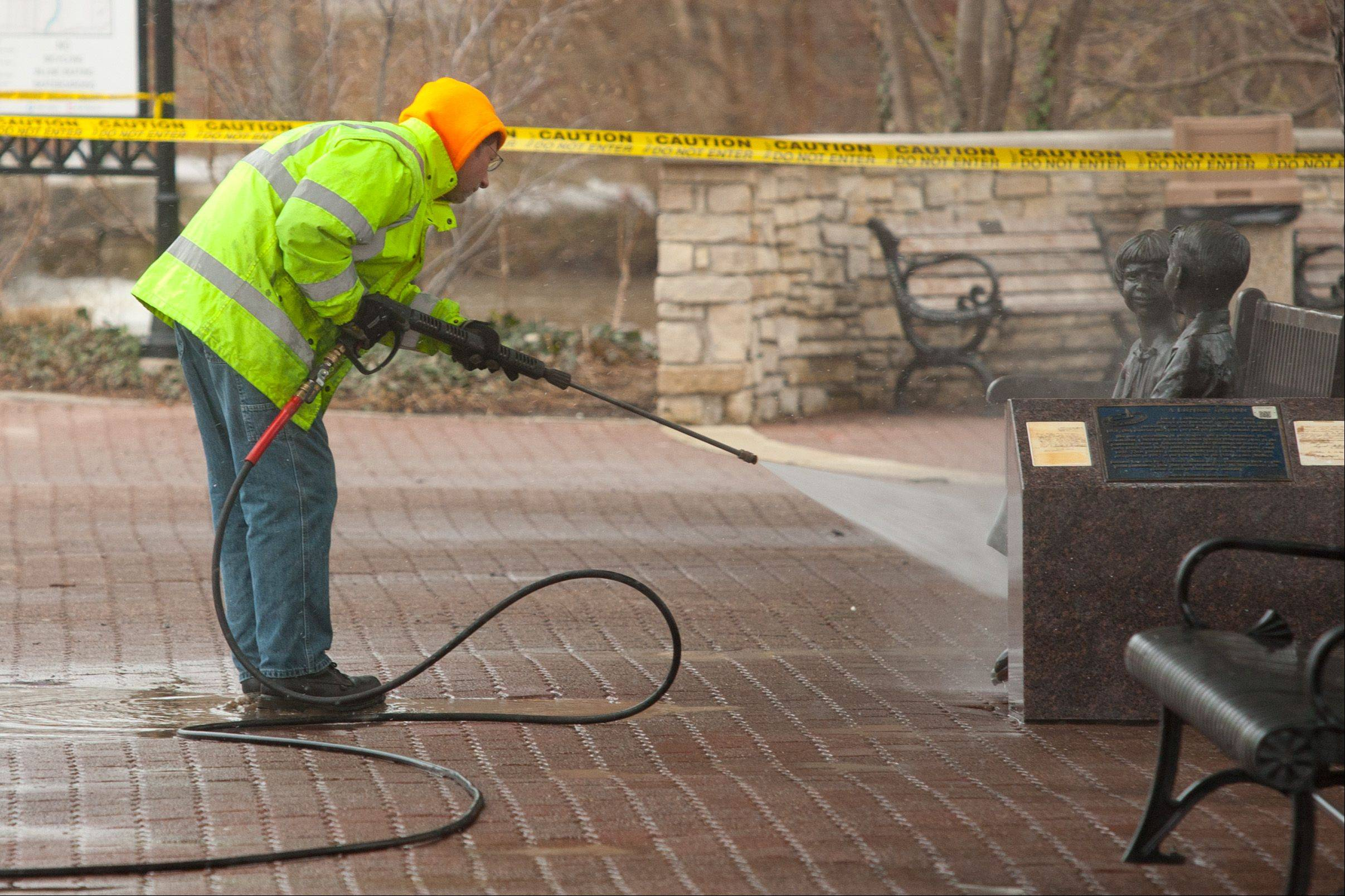 Public works employee Scott Kulak power washes, as the city of Naperville works to clean up from ravaging downtown flooding.
