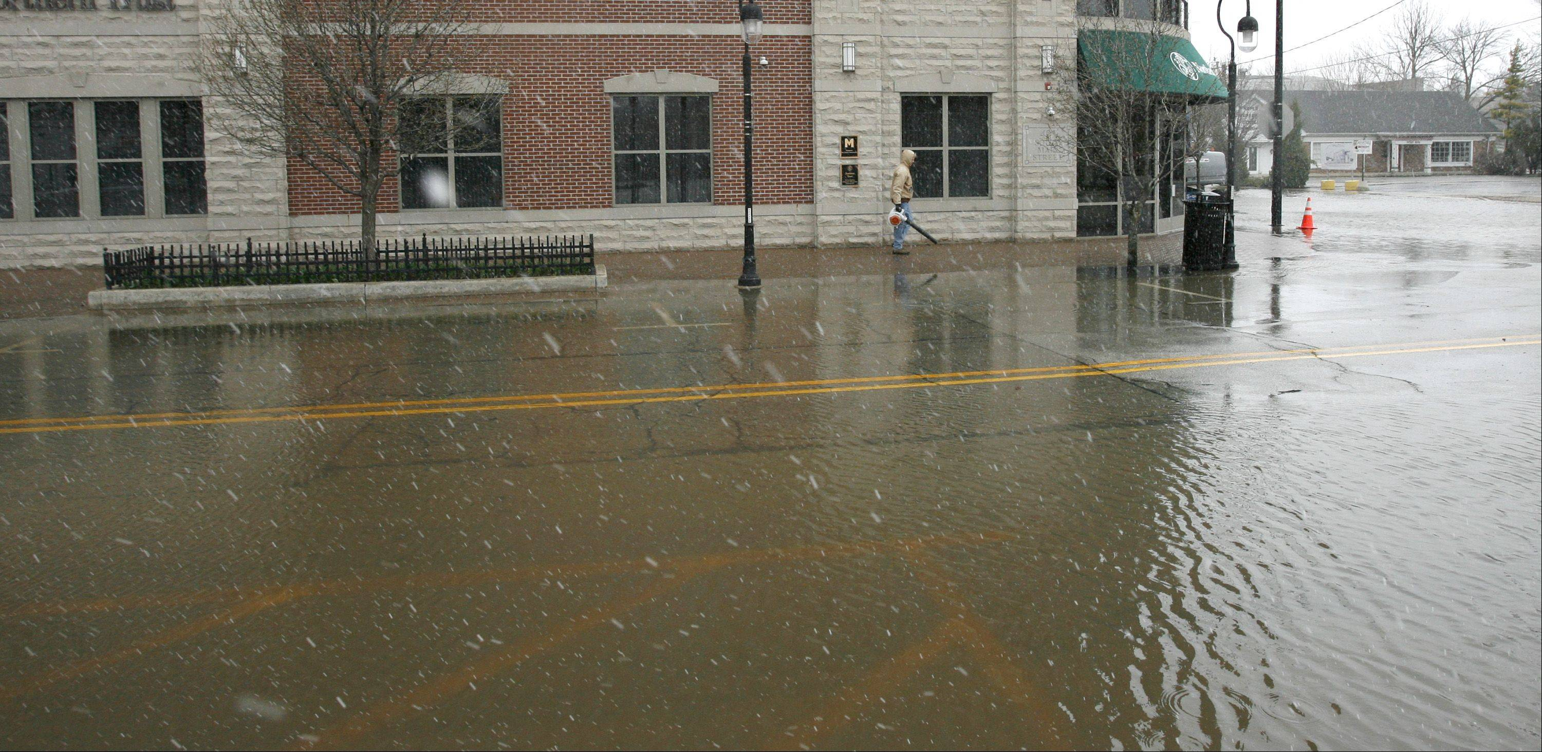 Snow falls, as the city of Naperville works to clean up from downtown flooding.
