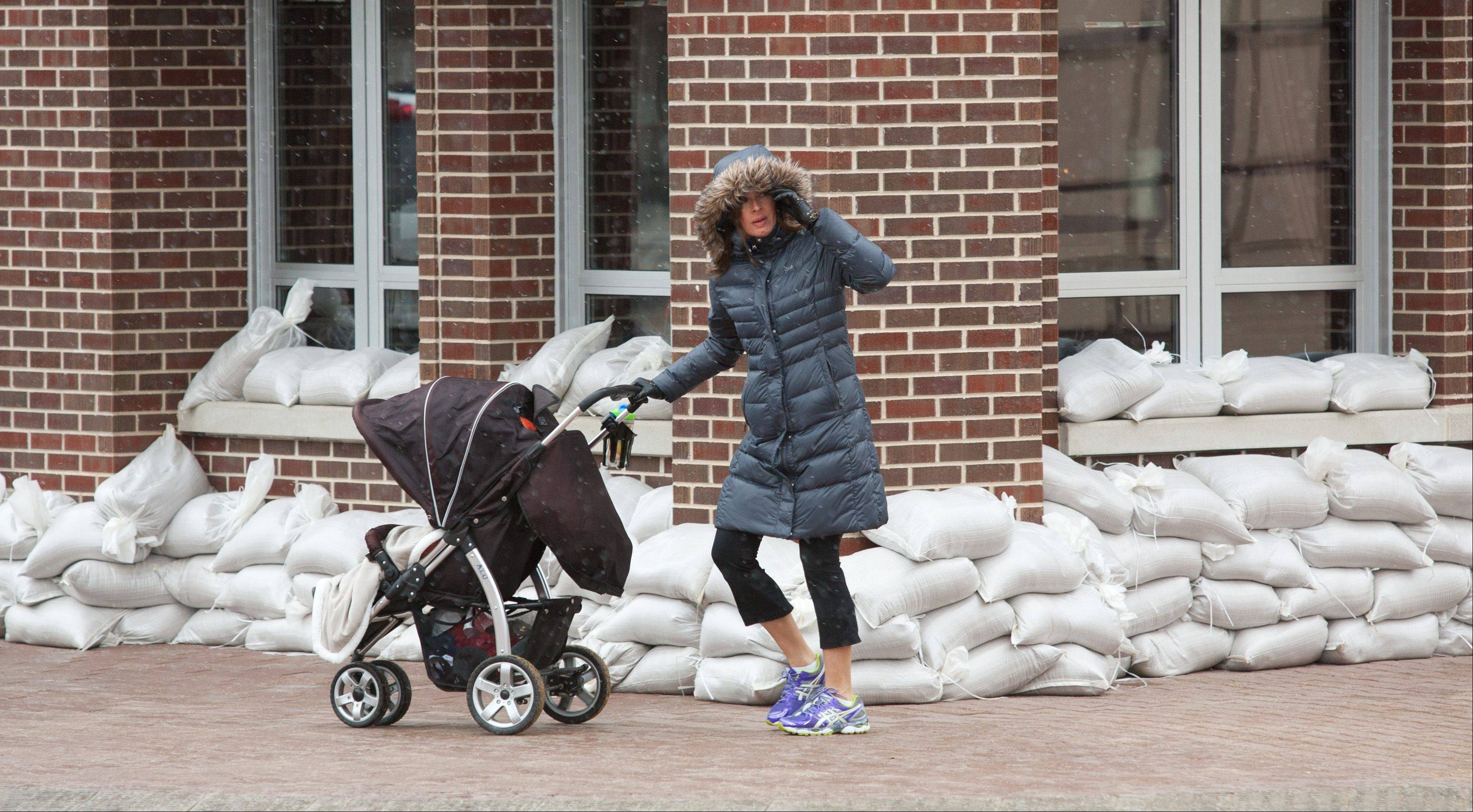 Snow falls in front of Sullivans, as a mom walks her baby while the city of Naperville works to clean up from ravaging downtown flooding.
