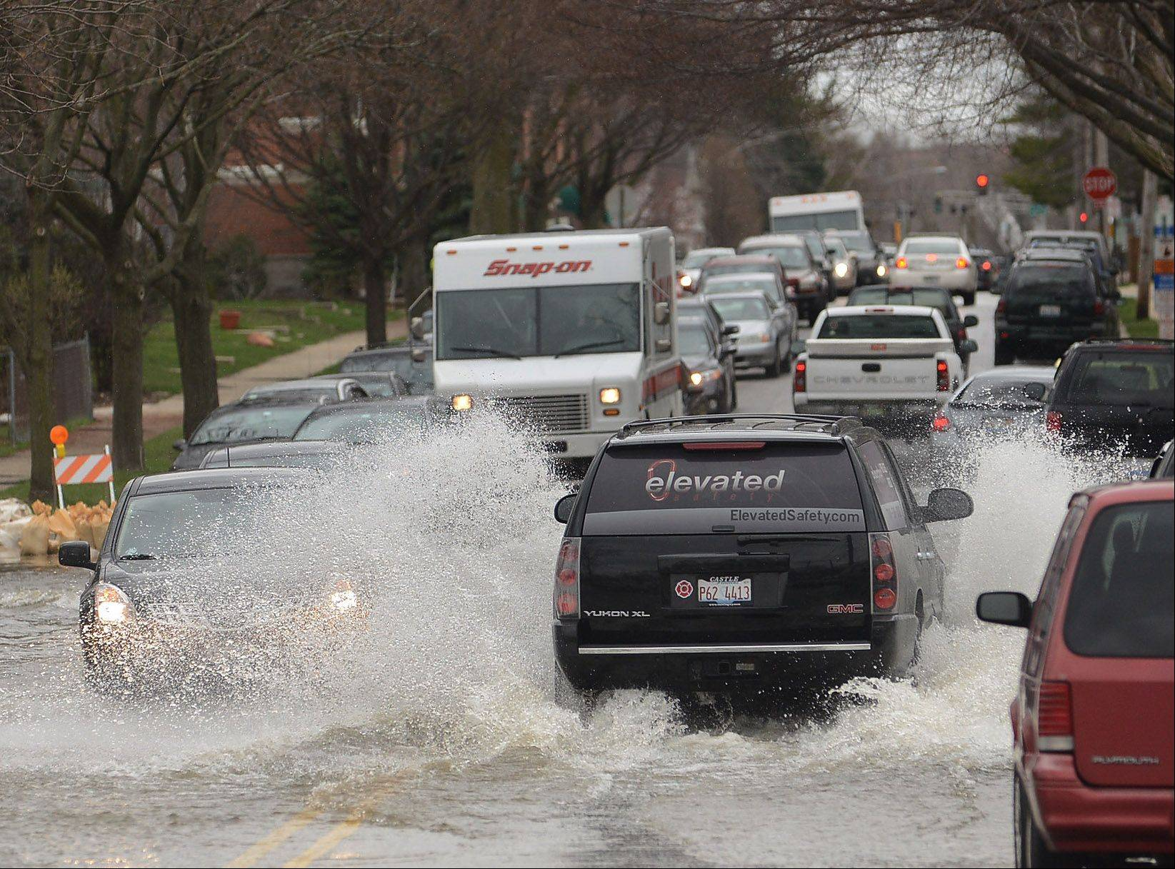 Cars try to plow through the water of a flooded Graceland Avenue in Des Plaines.