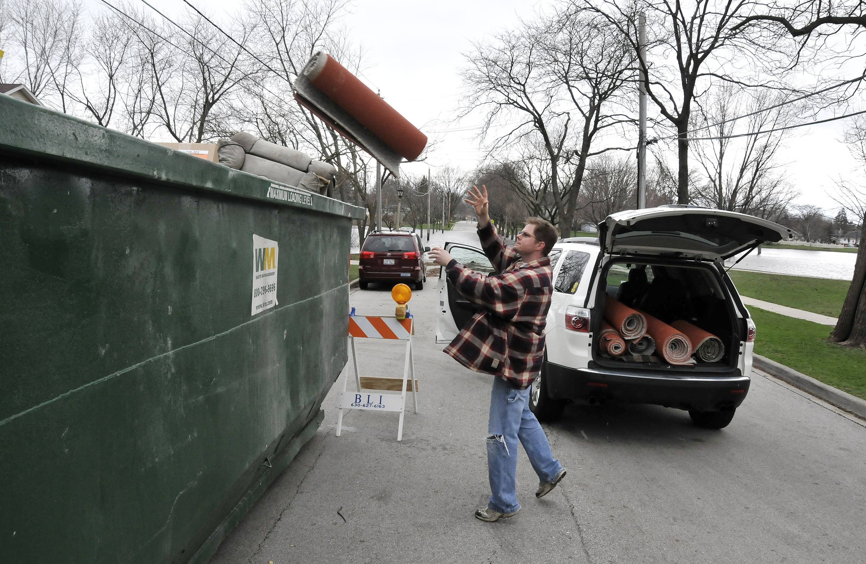 Terrace View Park in Lombard is still flooded over the banks, onto surrounding streets, and into surrounding basements. Greenfield Avenue by the park is one of several locations in Lombard where large dumpsters have been placed so residents can easily dispose of ruined items. Resident Kevin Reinheimer tosses his damaged carpet from his basement into the dumpster.