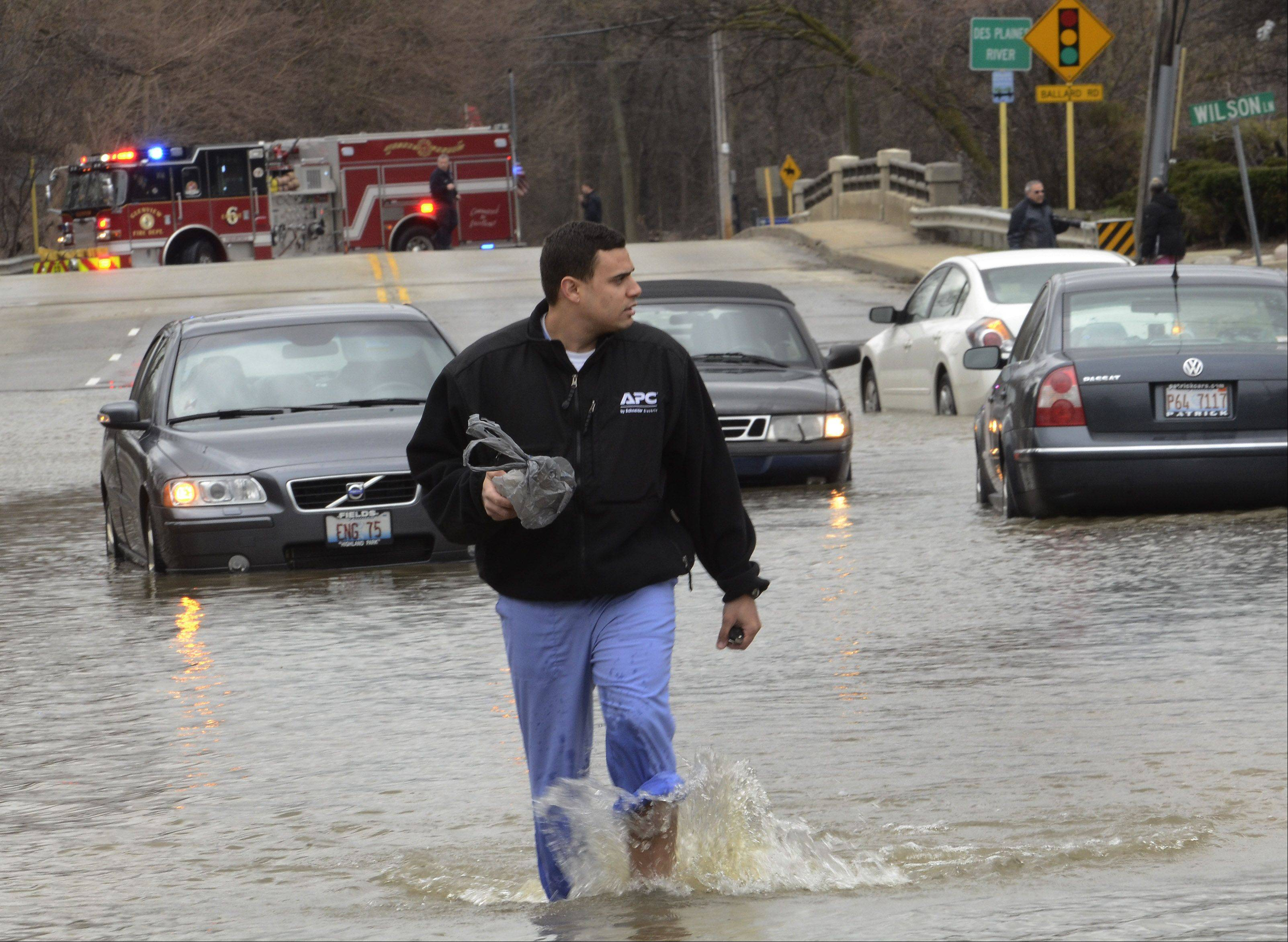 Efrain Baez of Des Plaines walks through the water after crawling out the trunk of his Volkswagen after getting stuck in the flooded intersection of Rand and Wilson in Des Plaines.