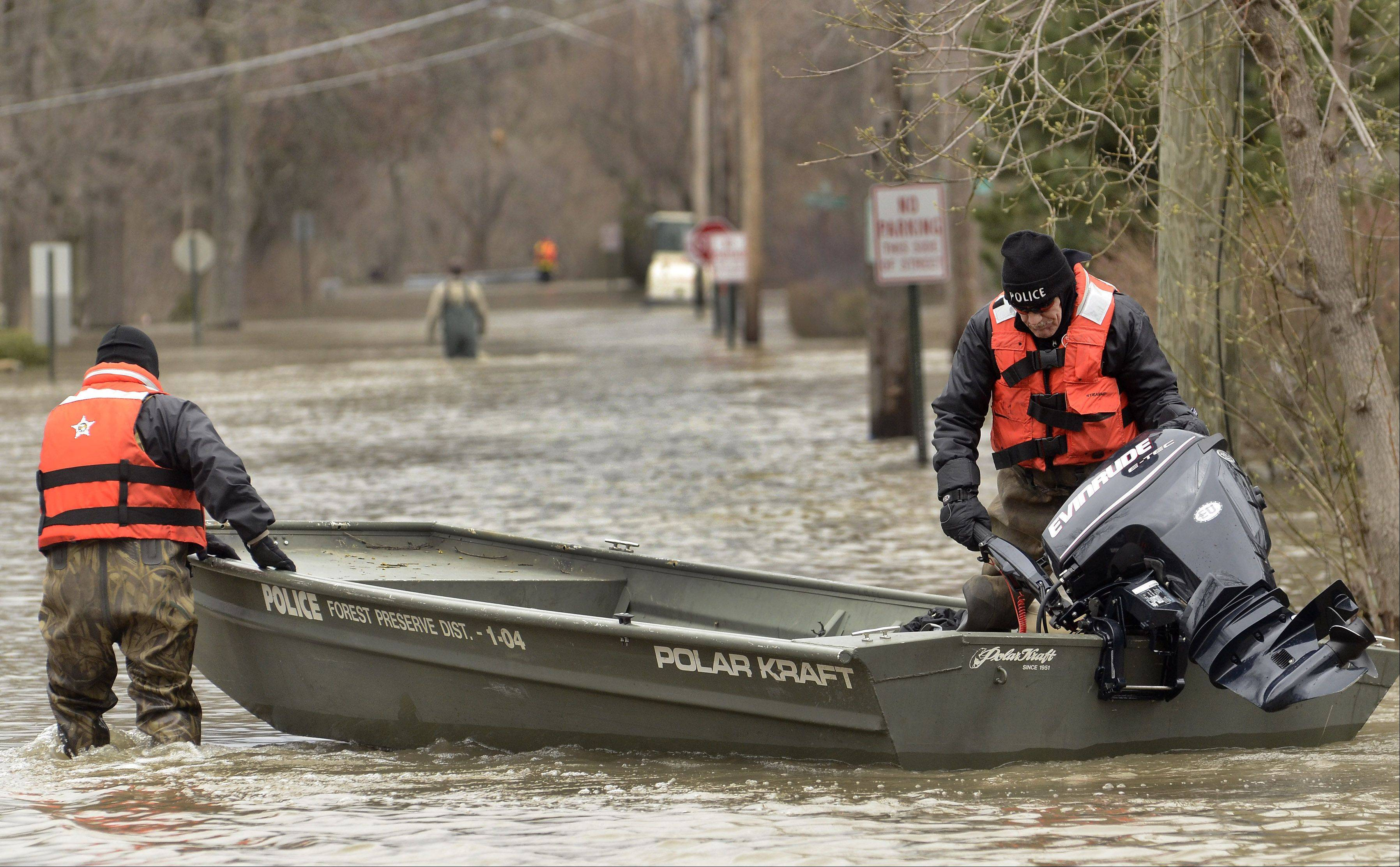 Cook County Forest Preserve Police use a boat to navigate Hawthorne Lane in Des Plaines.