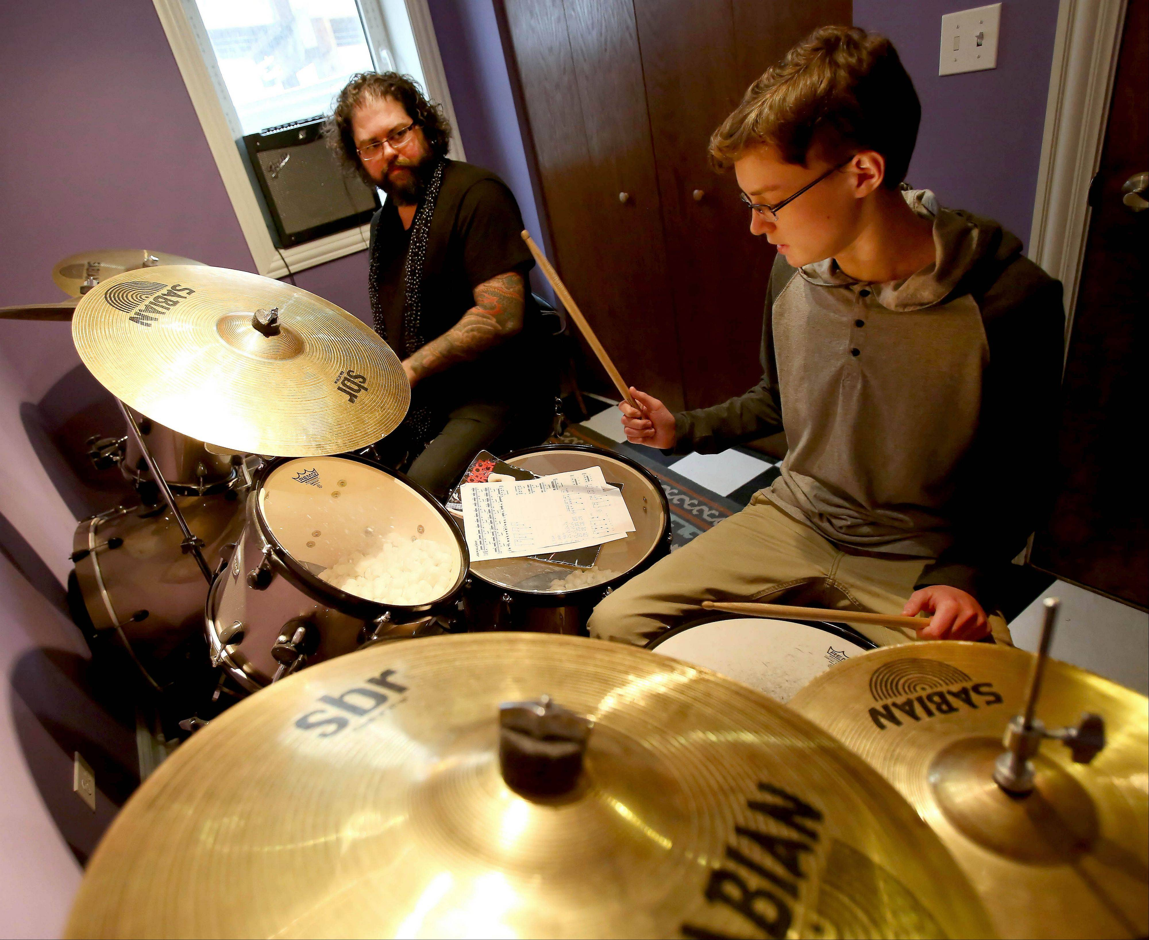 Harvey gives a lesson to James Turner, 15, of Bolingbrook at the School of Rock in Naperville.