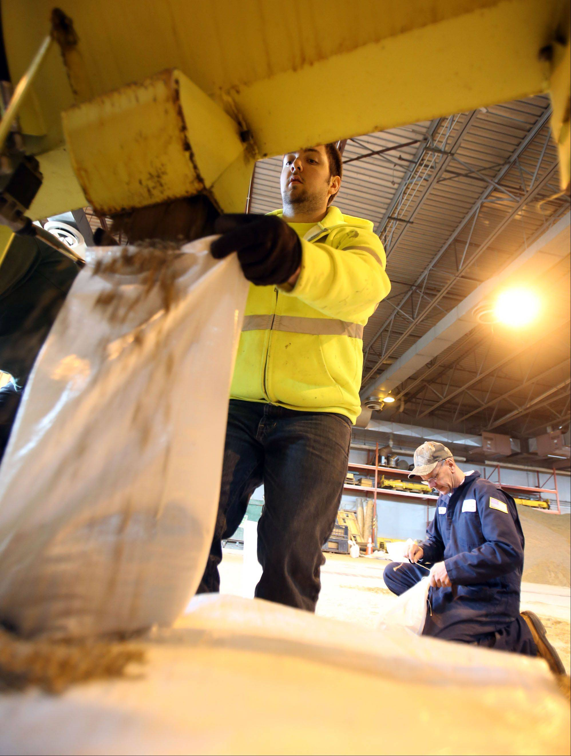 Lincolshire Public Works employees Frankie Martin, left, and Scott Malicki fill sand bags Friday morning.