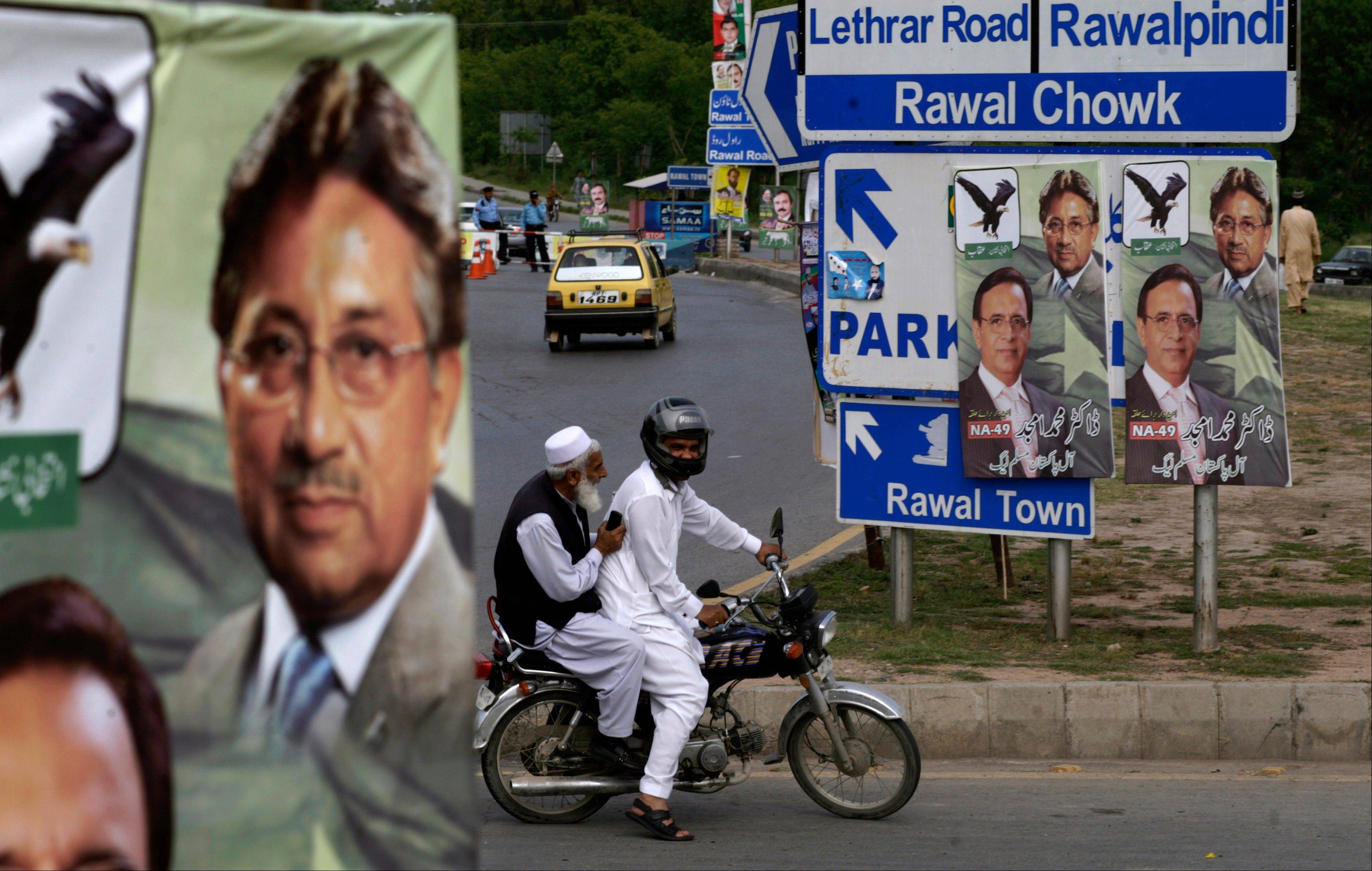 Pakistani men ride a motorcycle past posters showing former President and military ruler Pervez Musharraf, in Islamabad, Pakistan, Friday, April 19, 2013. Police arrested Musharraf overnight at his home in the capital, where he had holed up following a dramatic escape from court to avoid being detained, officials said Friday.