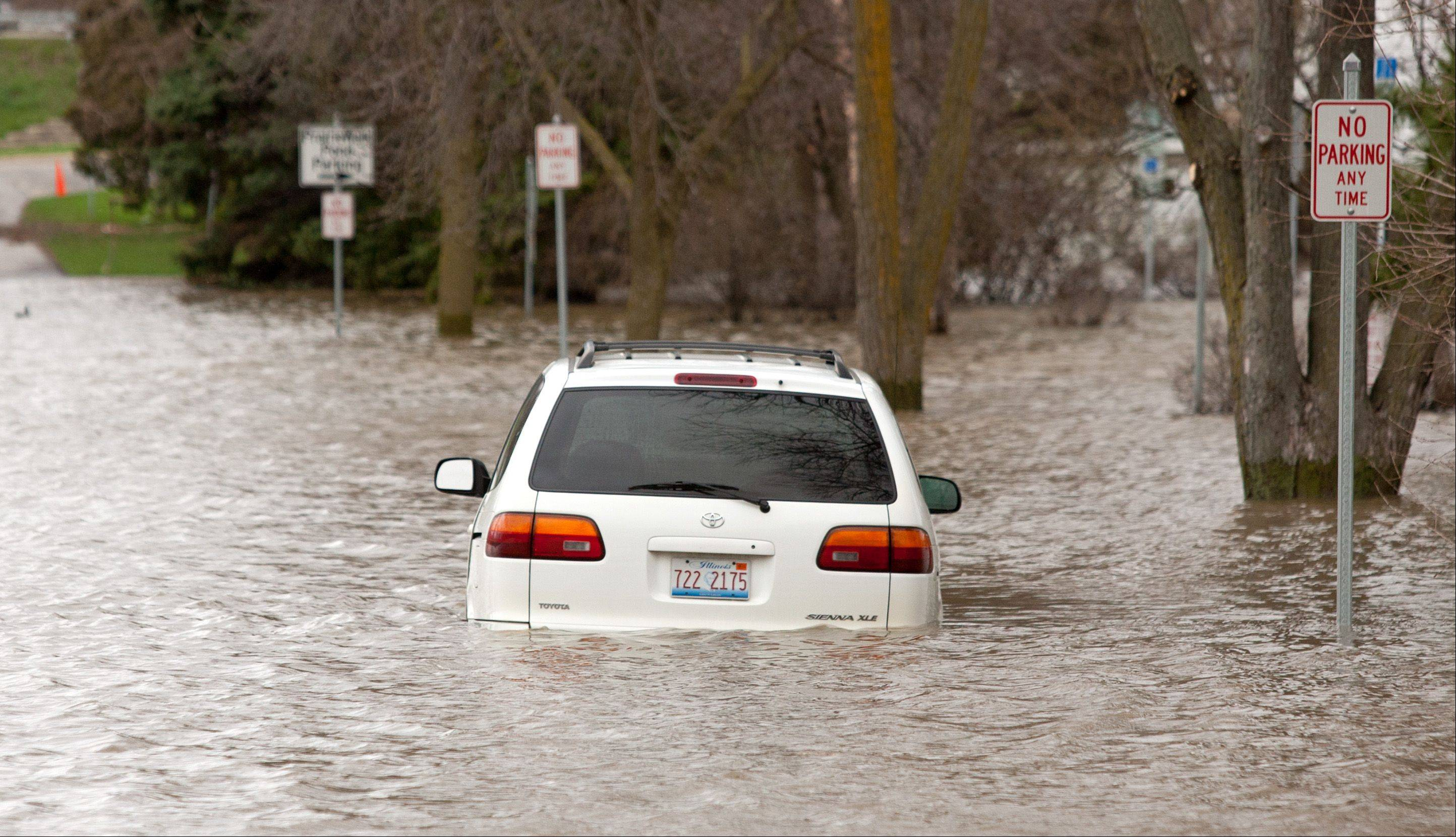A car remains partially submerged on Garfield Avenue just north of Burlington Avenue in downtown Lisle.