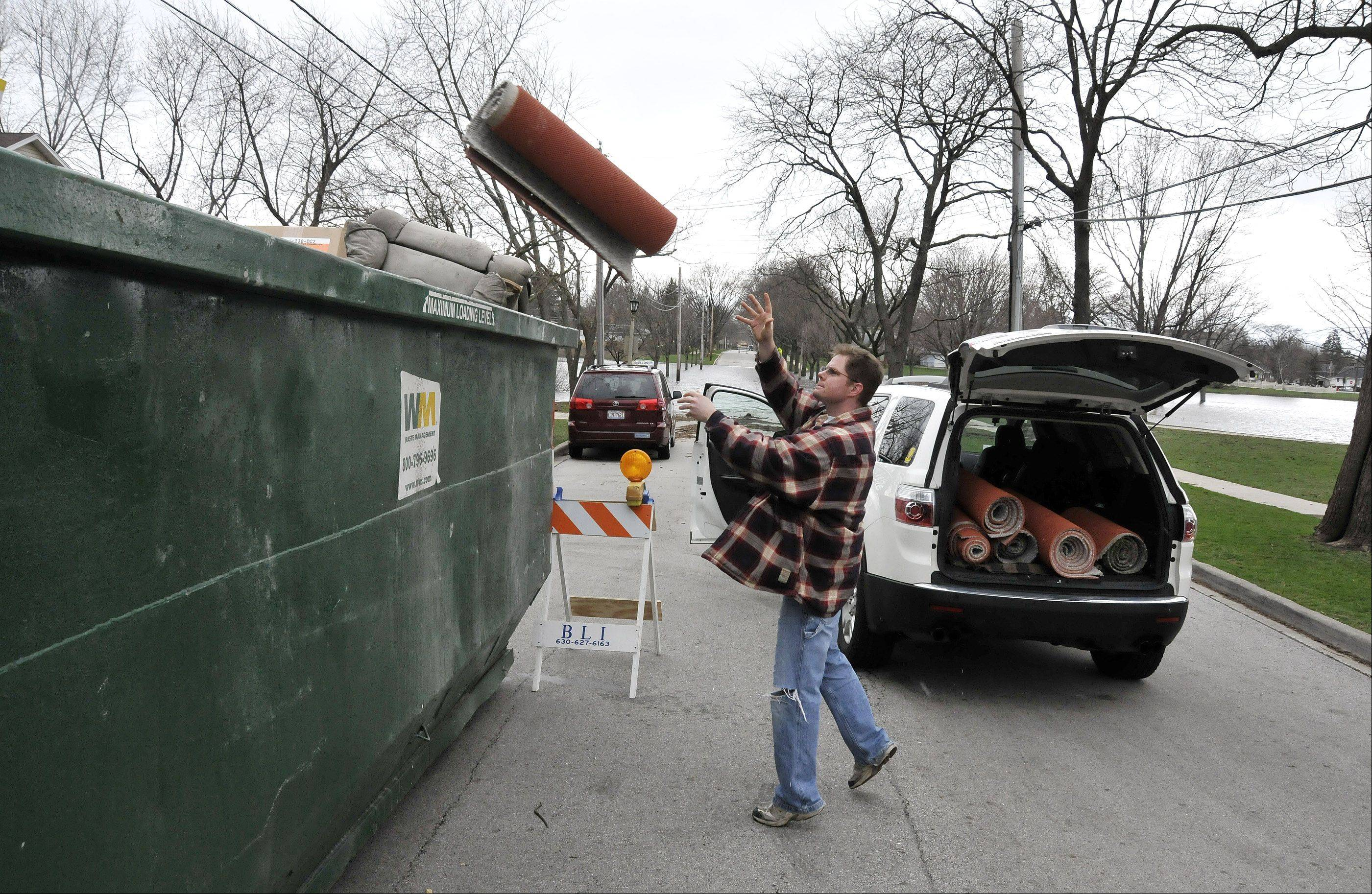 Terrace View Park in Lombard is still flooded over the banks, onto surrounding streets and into surrounding basements. Greenfield Avenue by the park is one of several locations in Lombard where large garbage bins have been placed to assist residents in disposing of ruined items. Kevin Reinheimer gets rid of his damaged carpet.
