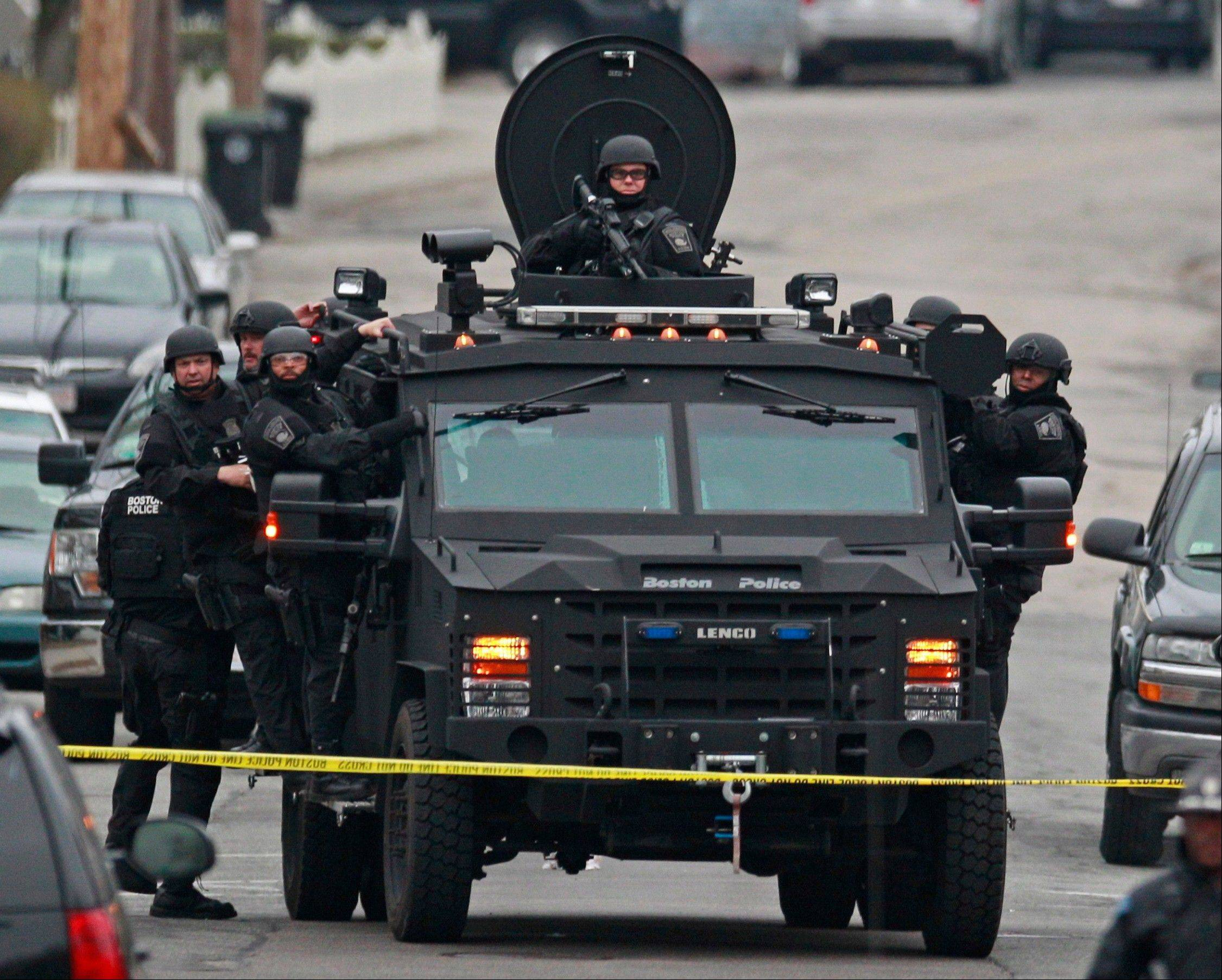 Police in tactical gear arrive on an armored police vehicle as they surround an apartment building while looking for a suspect in the Boston Marathon bombings in Watertown, Mass., Friday, April 19, 2013. The bombs that blew up seconds apart near the finish line of the Boston Marathon left the streets spattered with blood and glass, and gaping questions of who chose to attack and why.