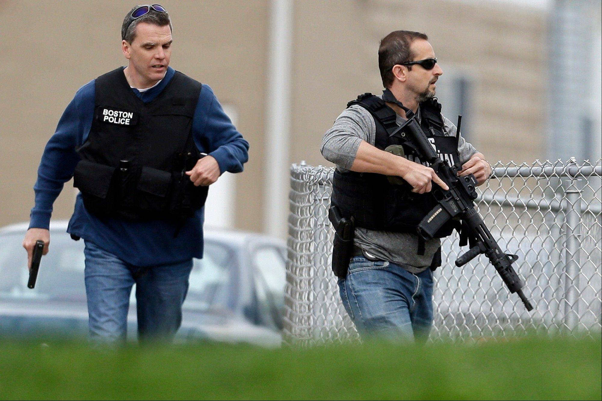 Police run with their weapons drawn as they conduct a search for a suspect in the Boston Marathon bombings, Friday, April 19, 2013, in Watertown, Mass. Two suspects in the Boston Marathon bombing killed an MIT police officer, injured a transit officer in a firefight and threw explosive devices at police during a getaway attempt in a long night of violence that left one of them dead and another still at large Friday, authorities said as the manhunt intensified for a young man described as a dangerous terrorist.