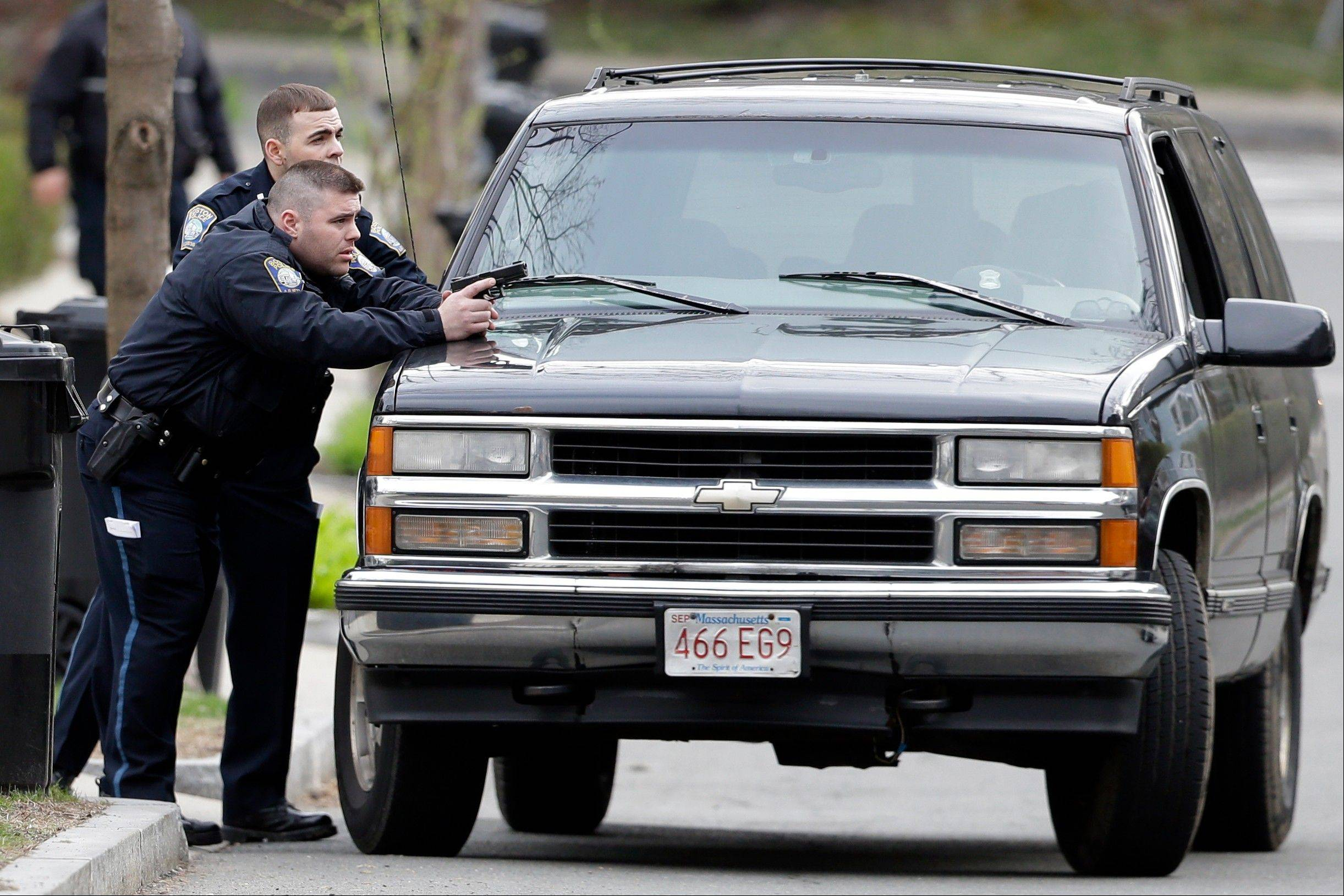 Police officers take cover as they conduct a search for a suspect in the Boston Marathon bombings, Friday, April 19, 2013, in Watertown, Mass. The two suspects in the Boston Marathon bombing killed an MIT police officer and hurled explosives at police in a car chase and gunbattle overnight that left one of them dead and his brother on the loose, authorities said Friday as thousands of officers swarmed the streets in a manhunt that all but paralyzed the Boston area.