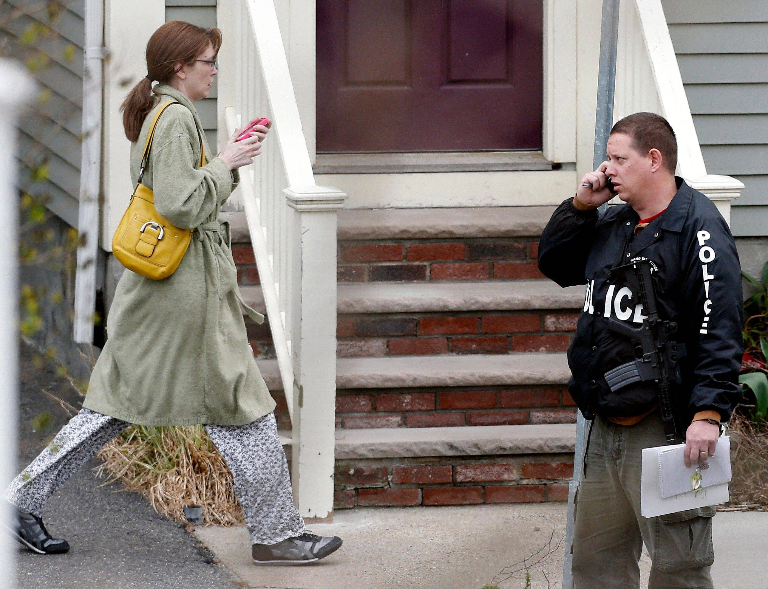 A woman heads away from a building in Cambridge, Mass., after being evacuated by police from her home next door, Friday, April 19, 2013. Two suspects in the Boston Marathon bombing killed an MIT police officer, injured a transit officer in a firefight and threw explosive devices at police during a getaway attempt in a long night of violence that left one of them dead and another still at large Friday, authorities said as the manhunt intensified for a young man described as a dangerous terrorist.