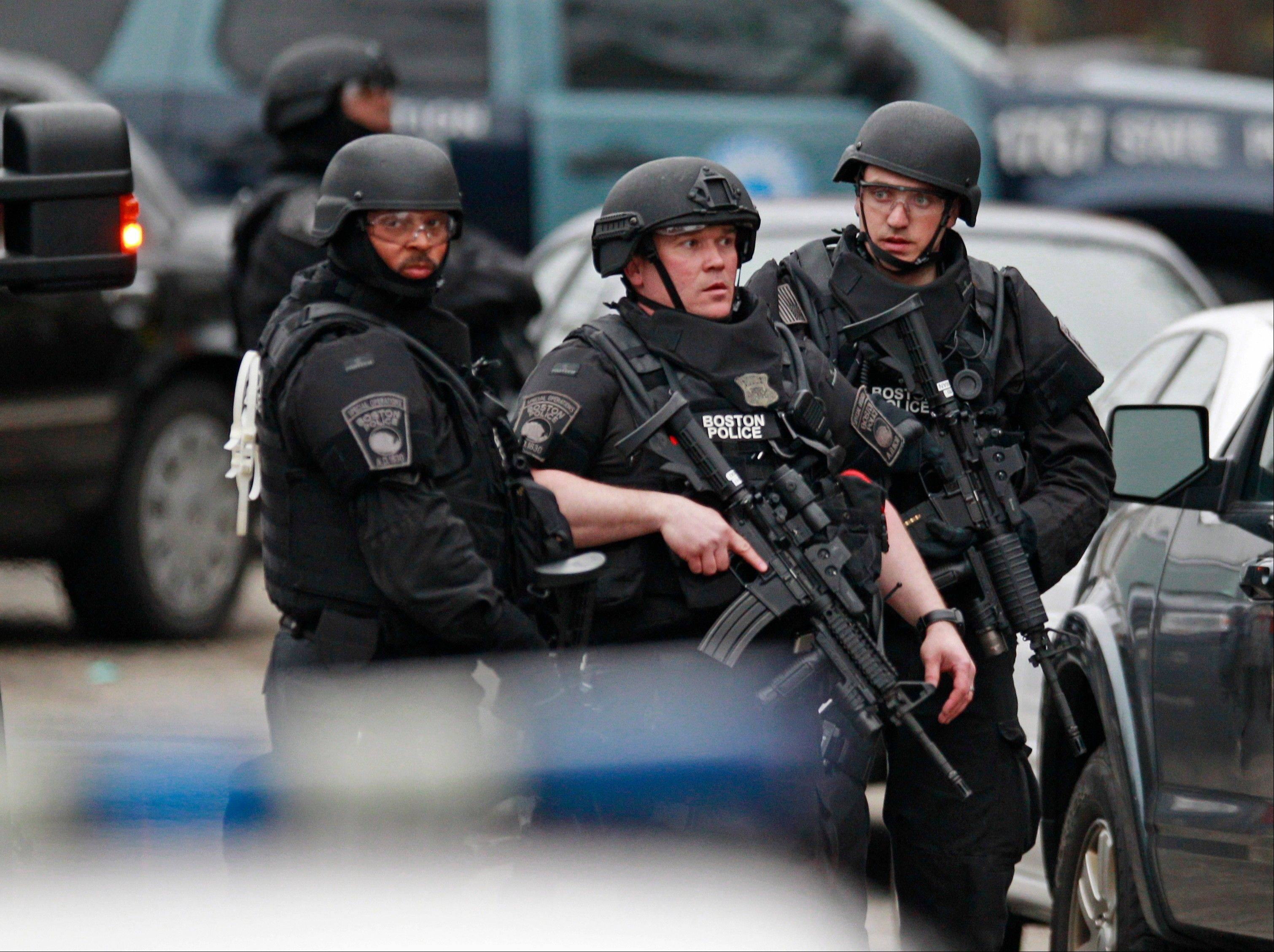 Police in tactical gear surround an apartment building while looking for a suspect in the Boston Marathon bombings in Watertown, Mass., Friday, April 19, 2013. The bombs that blew up seconds apart near the finish line of the Boston Marathon left the streets spattered with blood and glass, and gaping questions of who chose to attack and why.