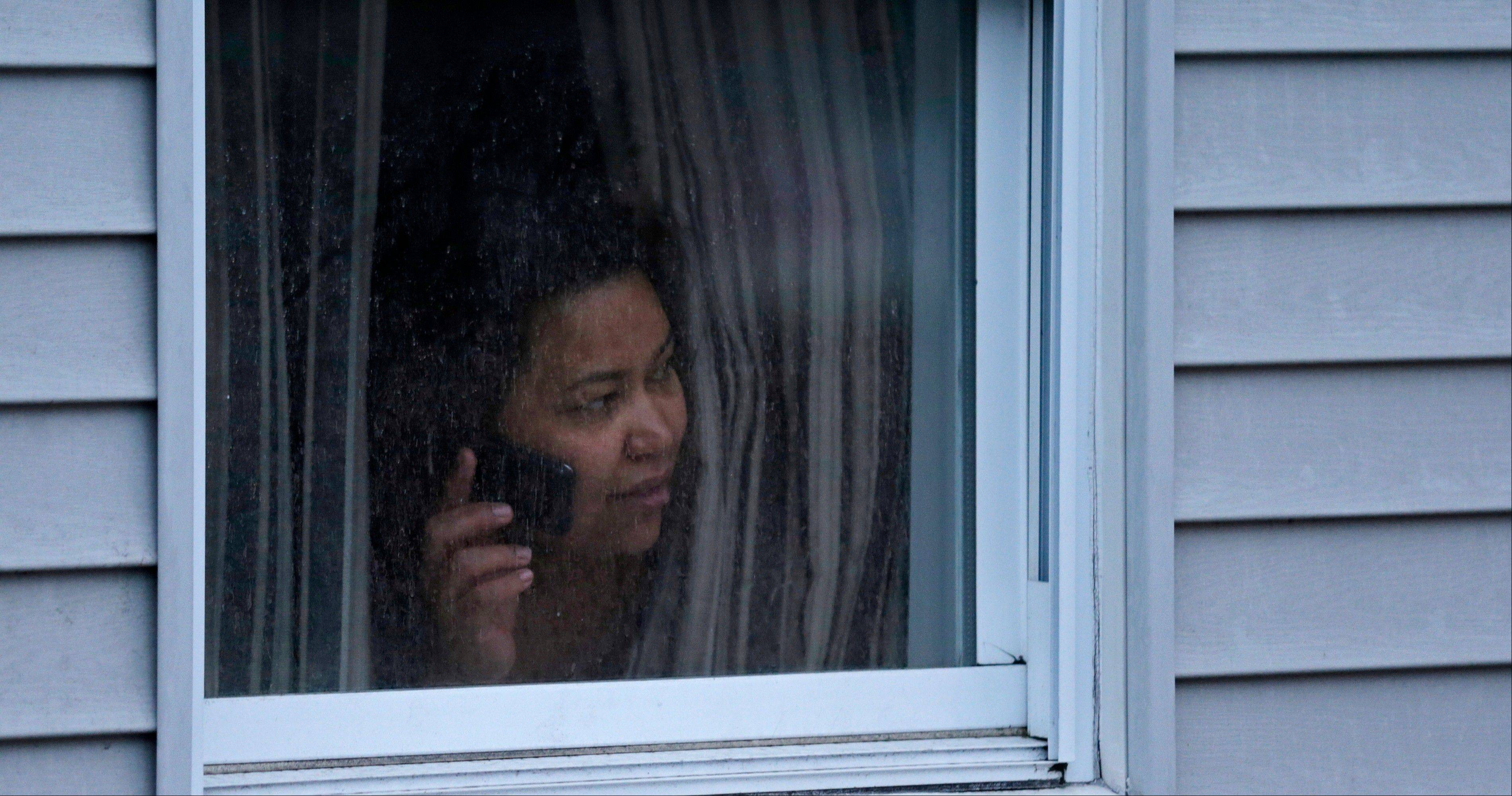A woman looks out a window at her home as police start to search an apartment building while looking for a suspect in the Boston Marathon bombings in Watertown, Mass., Friday, April 19, 2013. Two suspects in the Boston Marathon bombing killed an MIT police officer, injured a transit officer in a firefight and threw explosive devices at police during their getaway attempt in a long night of violence that left one of them dead and another still at large Friday, authorities said as the manhunt intensified for a young man described as a dangerous terrorist.