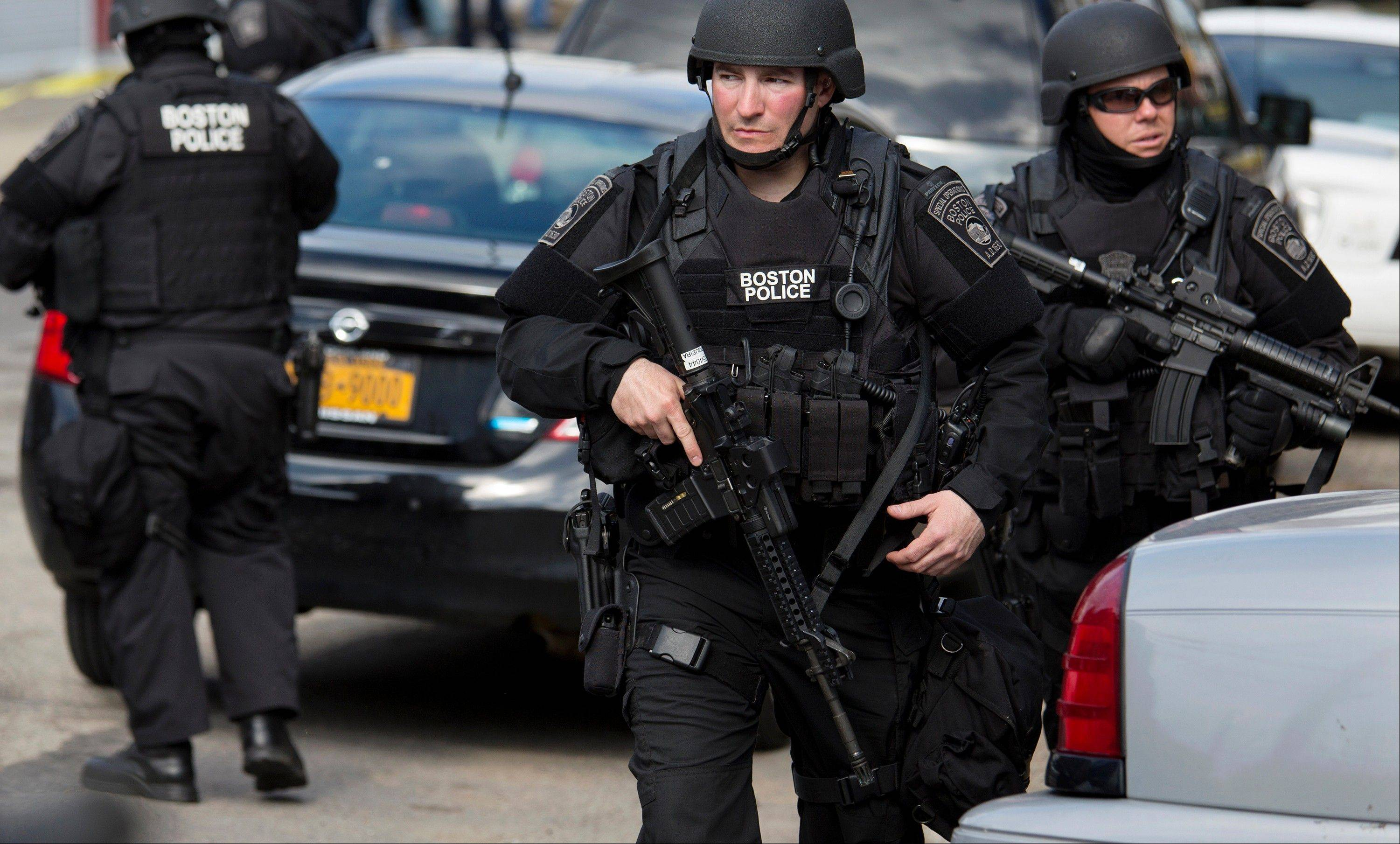 Heavily armed police continue to patrol the neighborhoods of Watertown, Mass. Friday, April 19, 2013, as they continue a massive search for one of two suspects in the Boston Marathon bombing. A second suspect died in the early morning hours after an encounter with law enforcement.