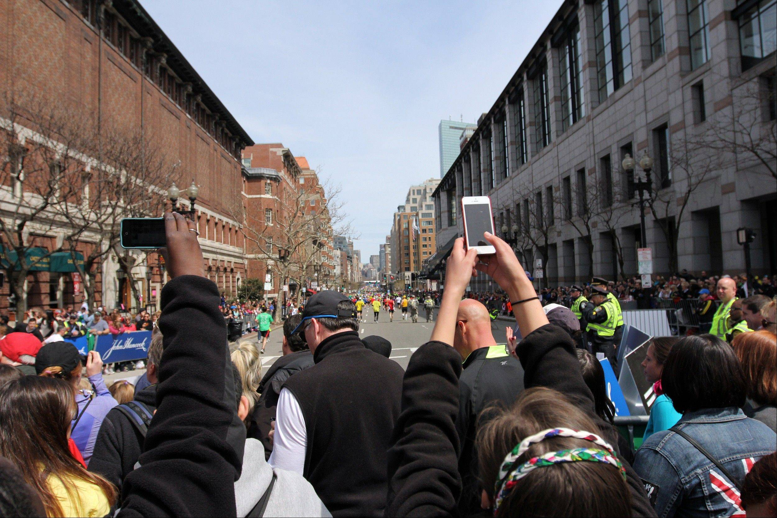 Spectators take pictures with camera phones during the Boston Marathon in Boston, before two bombs exploded at the finish line in an attack that killed 3 people and wounded over 170.