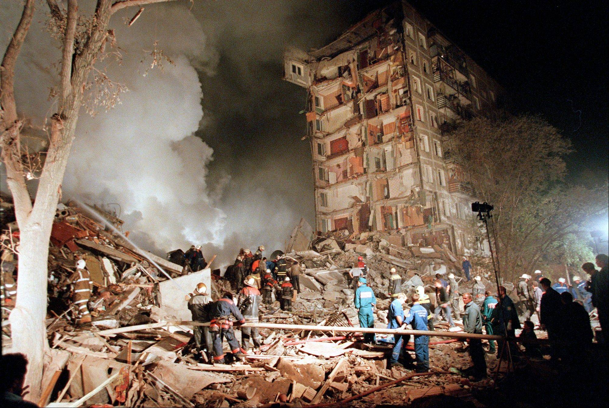 In this early Thursday, Sept. 9, 1999 file photo smoke rises from an apartment building destroyed by a bomb blast blamed on Chechen militants, as Russian Emergency Situations Ministry officers and firefighters try to save people in Moscow.
