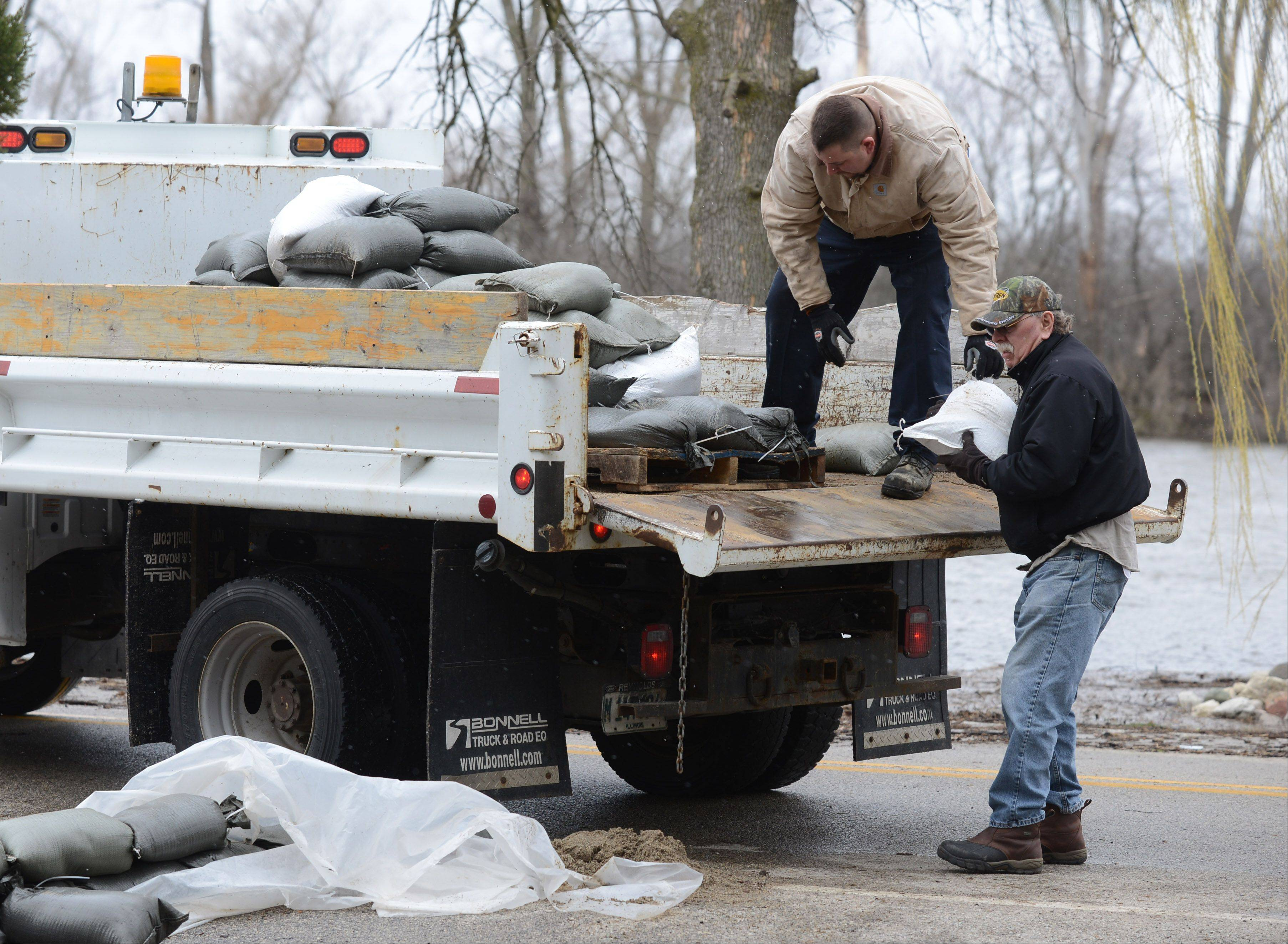 Eric Chesler, left, with the Nunda Township Highway Department, and volunteer Greg Tricker deliver sandbags to homeowners on Rawson Bridge Road along the Fox River Friday morning.