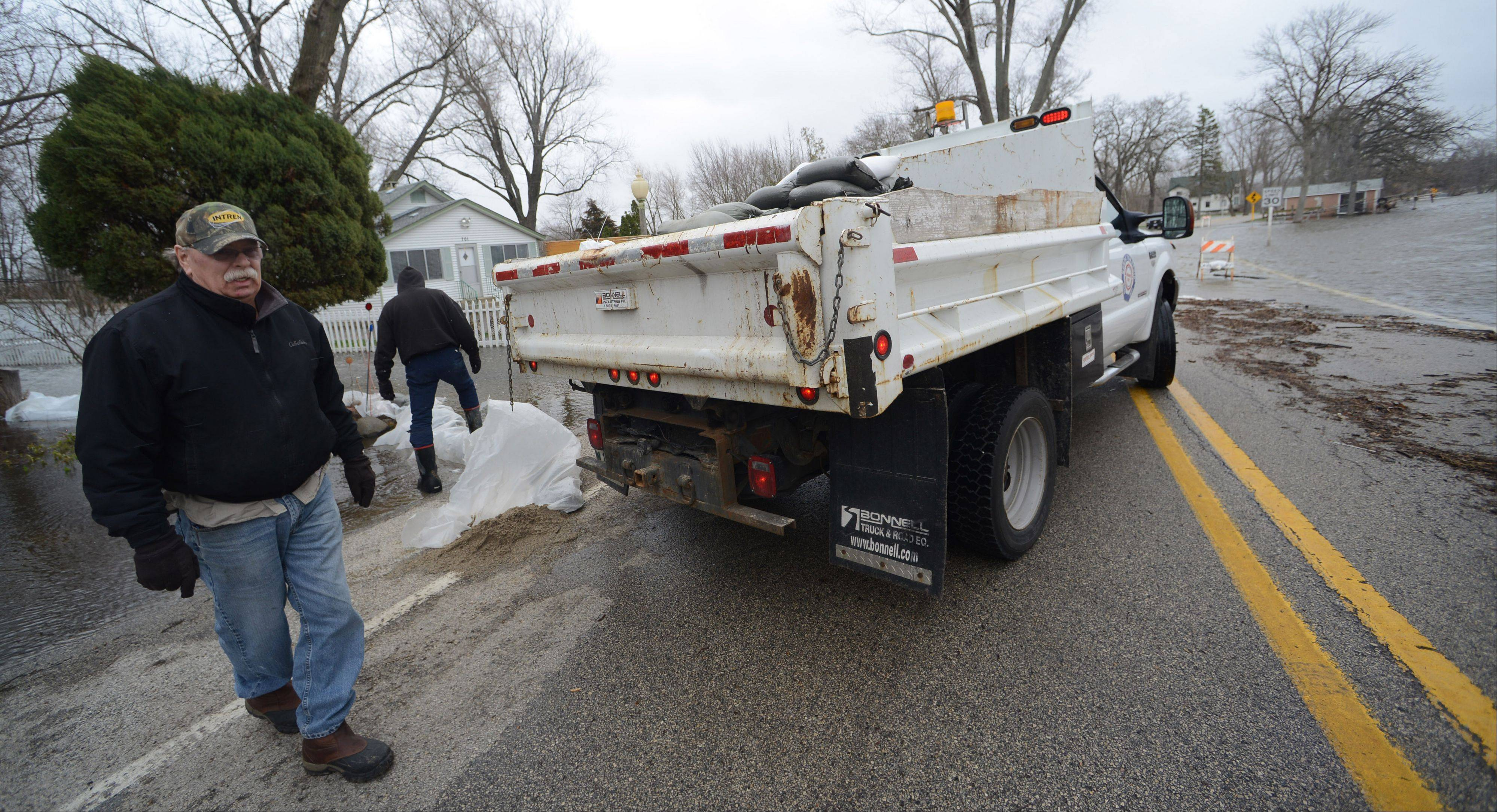 Volunteers work with the Nunda Township Highway Department Greg Tricker to deliver sandbags to homeowners on Rawson Bridge Road along the Fox River Friday morning.