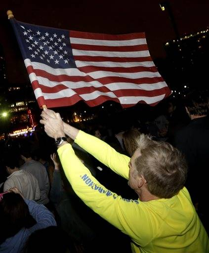 Frank McGillin, who ran three Boston Marathons, waves a U.S. flag as a crowd reacts to news of the arrest of one of the Boston Marathon bombing suspects during a celebration at Boston Common, Friday, April 19, 2013, in Boston. Boston Marathon bombing suspect Dzhokhar Tsarnaev was captured in Watertown, Mass. The 19-year-old college student wanted in the bombings was taken into custody Friday evening after a manhunt that left the city virtually paralyzed and his older brother and accomplice dead.