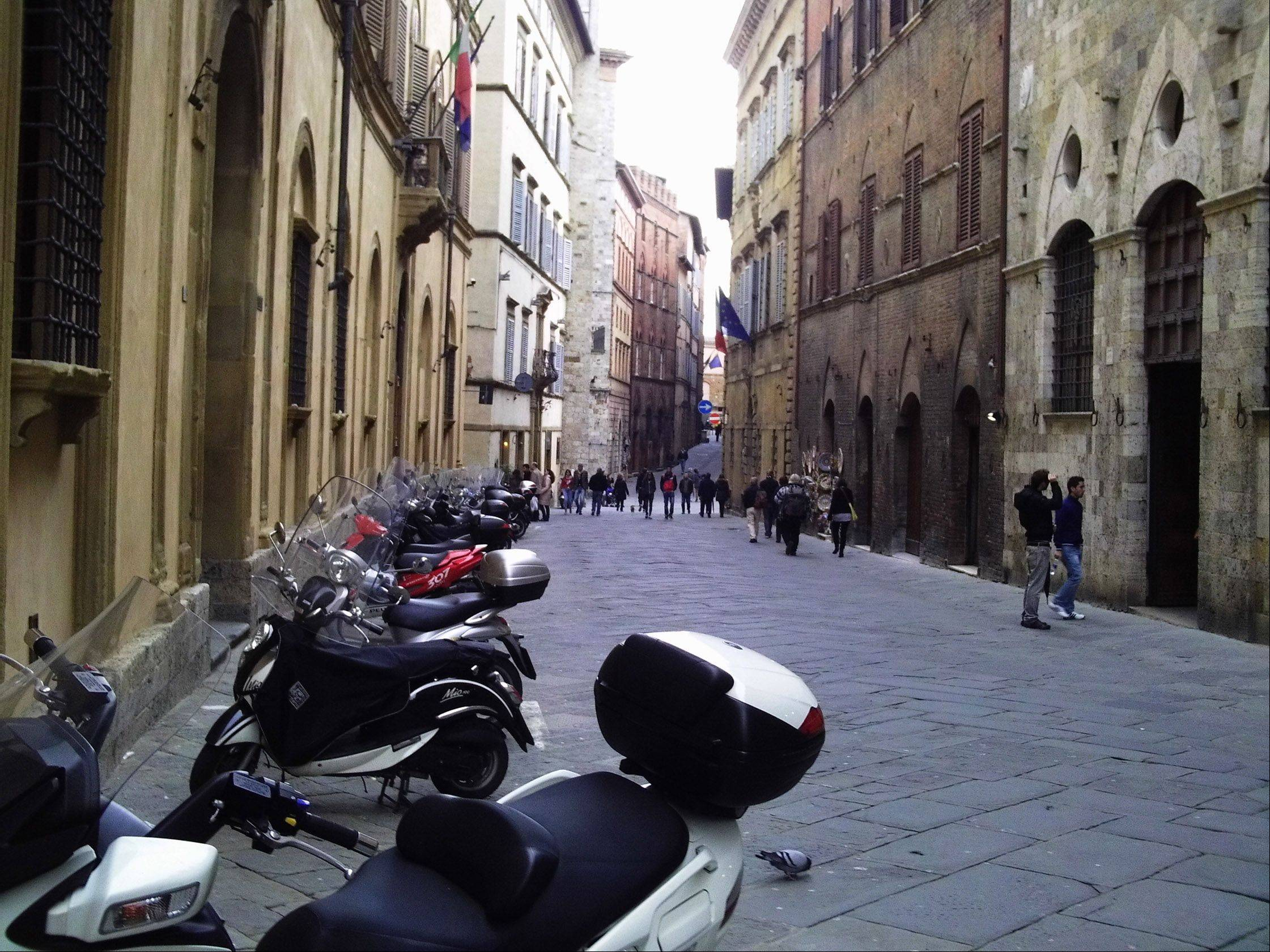 Scooters line a bricked street in Siena, Italy. The choir of Lake Zurich High School visited Italy in March and performed at the Vatican.