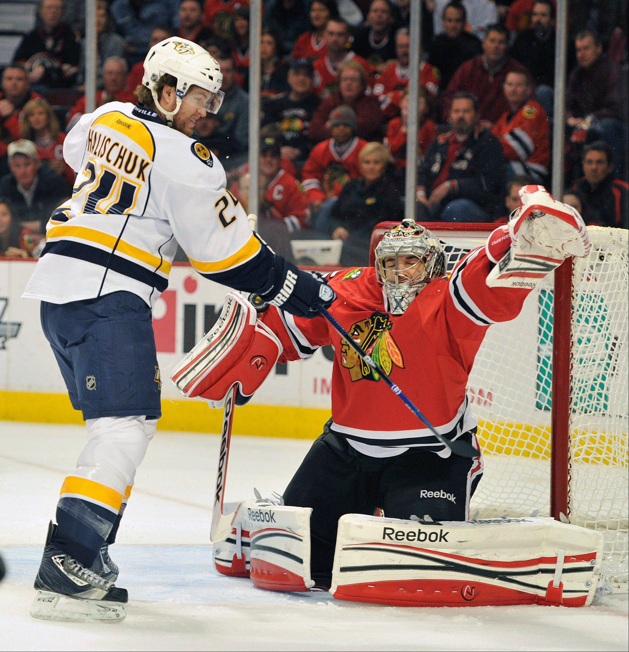 Nashville Predators' Matt Halischuk (24) tips the puck past the Chicago Blackhawks' Corey Crawford to score during the first period of an NHL hockey game on Friday, April 19, 2013, in Chicago.