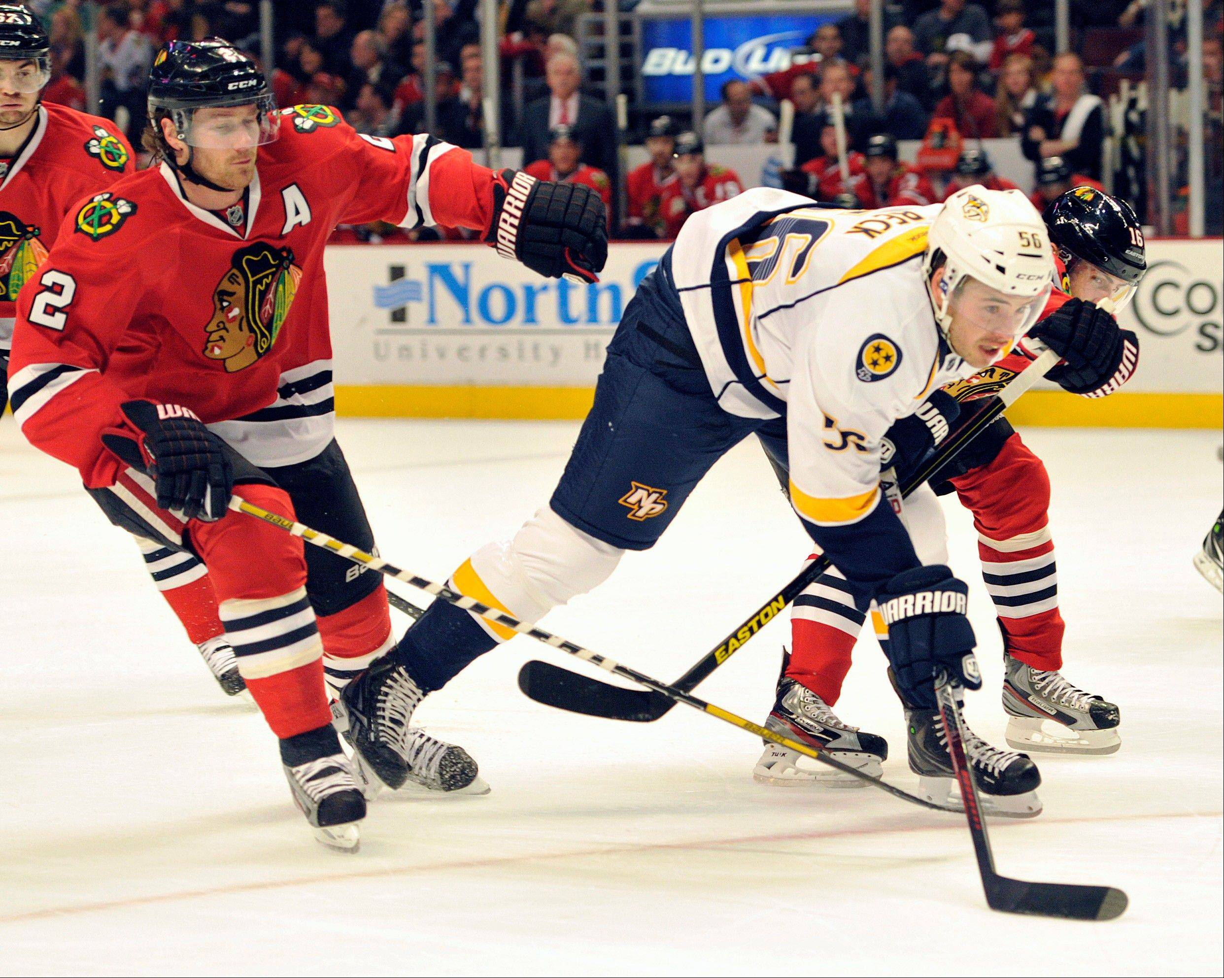 Chicago Blackhawks' Duncan Keith (2) checks the Nashville Predators' Taylor Beck as he reaches for the puck during the first period of an NHL hockey game Friday, April 19, 2013, in Chicago.