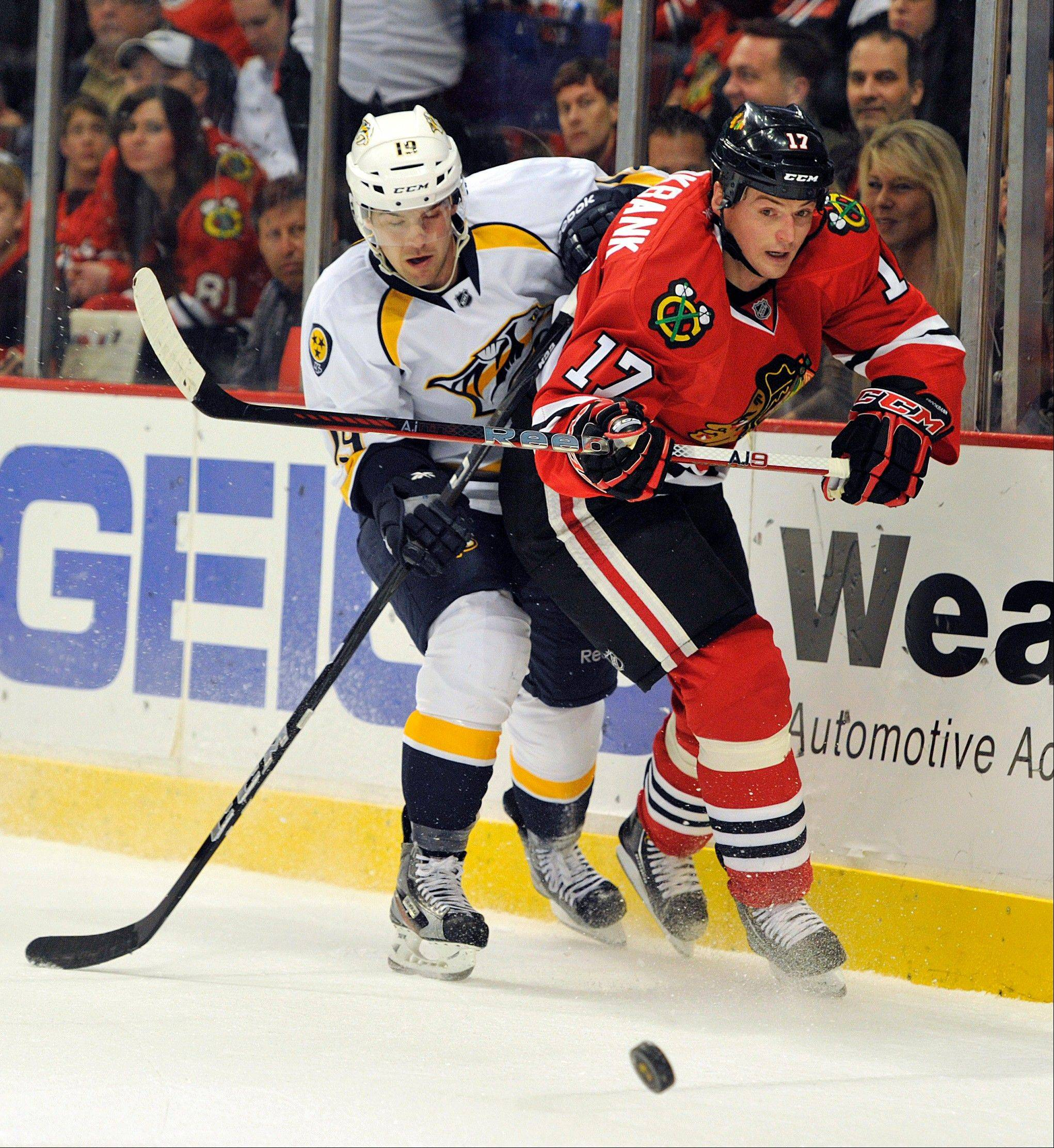 Nashville Predators' Bobby Butler left and the Chicago Blackhawks' Sheldon Brookbank (17) scramble for control of the puck during the first period of an NHL Hockey game Friday, April 19, 2013, in Chicago.